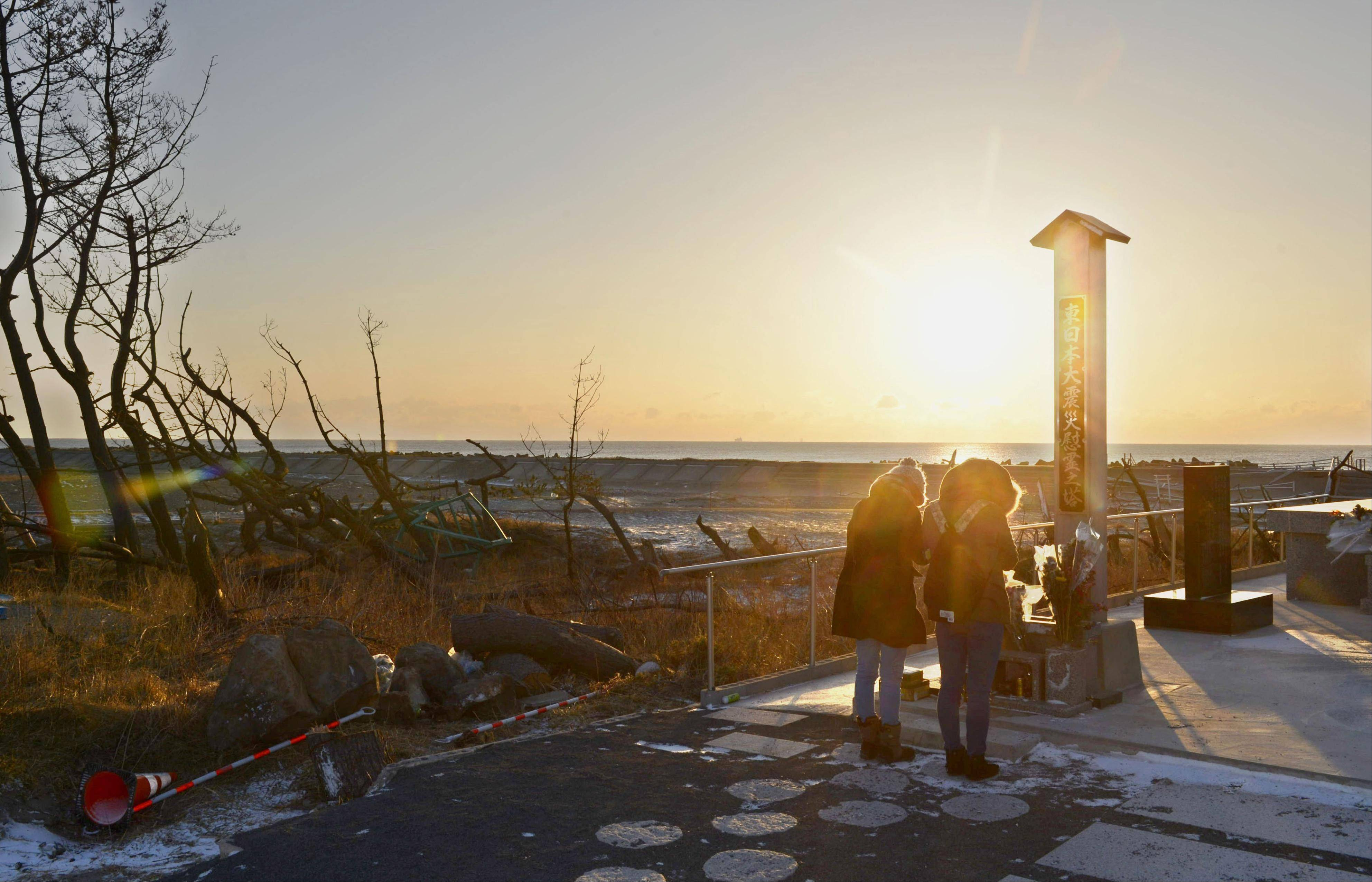 People offer prayers in front of a memorial cenotaph for tsunami victims on a beach in Arahama in Sendai, Miyagi Prefecture, Japan, Monday morning, March 11, 2013. Japan marked the second anniversary of its earthquake, tsunami and nuclear catastrophe, that killed nearly 19, 000 people in areas along Japan's northeastern coast.