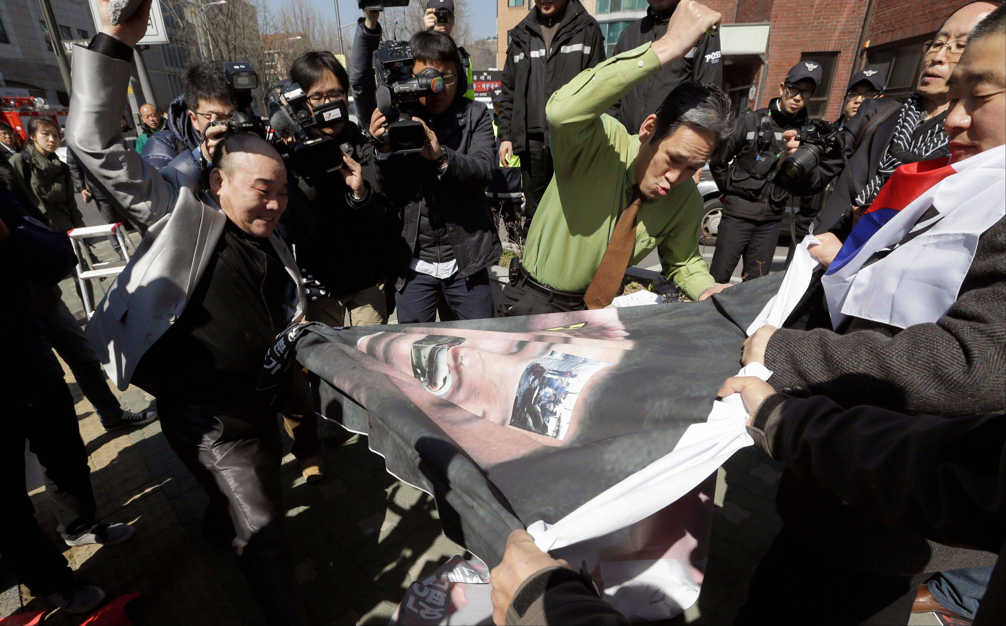 South Korean protesters hit a huge banner with a picture of North Korean leader Kim Jong Un during a rally denouncing North Korea's recent threat and supporting South Korean President Park Geun-hye near the presidential Blue House in Seoul, South Korea, Monday. South Korea and the U.S. began annual military drills Monday despite North Korean threats to respond by voiding the armistice that ended the Korean War and launching a nuclear attack on the U.S.