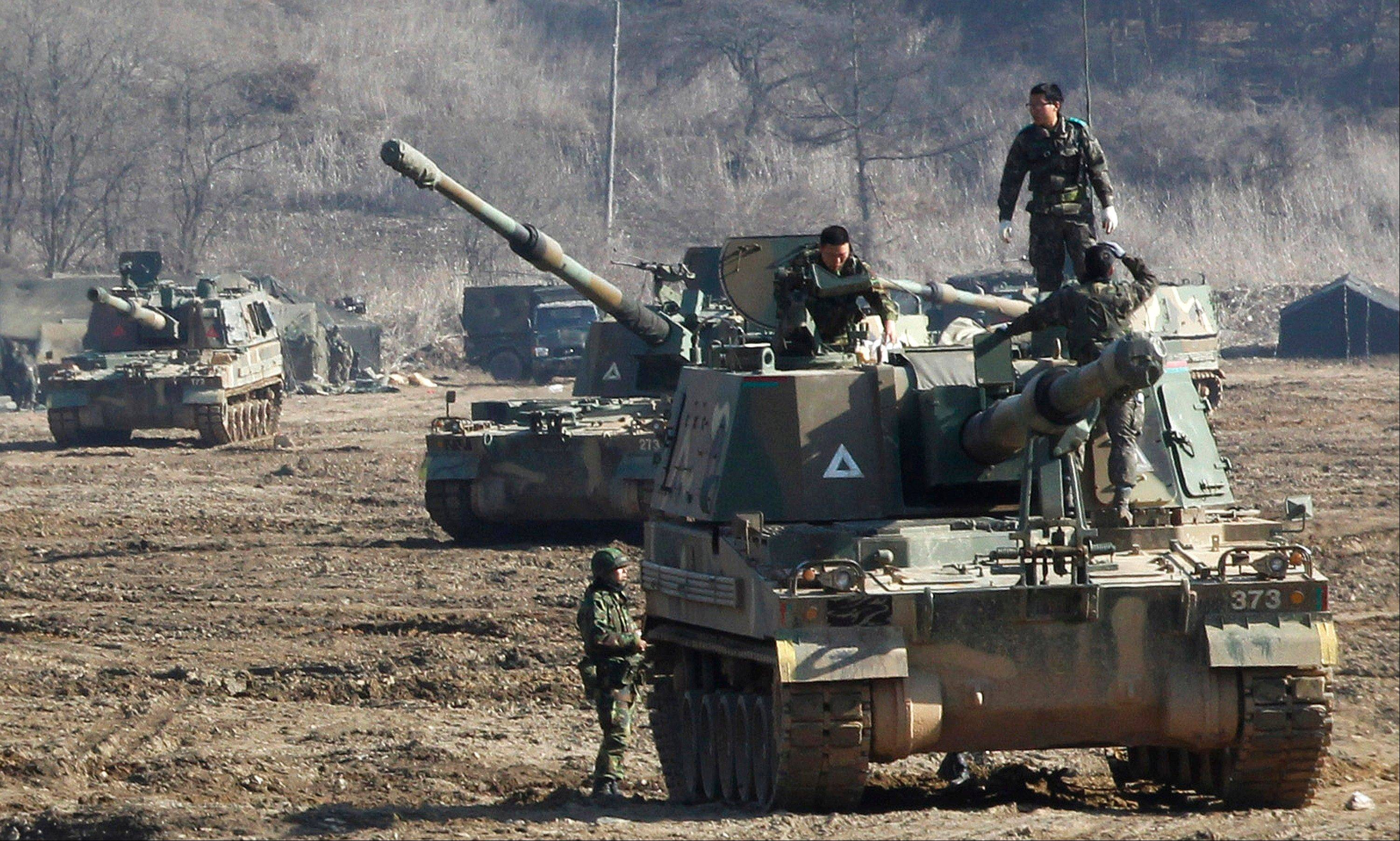 South Korean Army soldiers work on their K-9 self-propelled artillery vehicle during an exercise against possible attacks by North Korea near the border village of Panmunjom in Paju, South Korea, Monday.