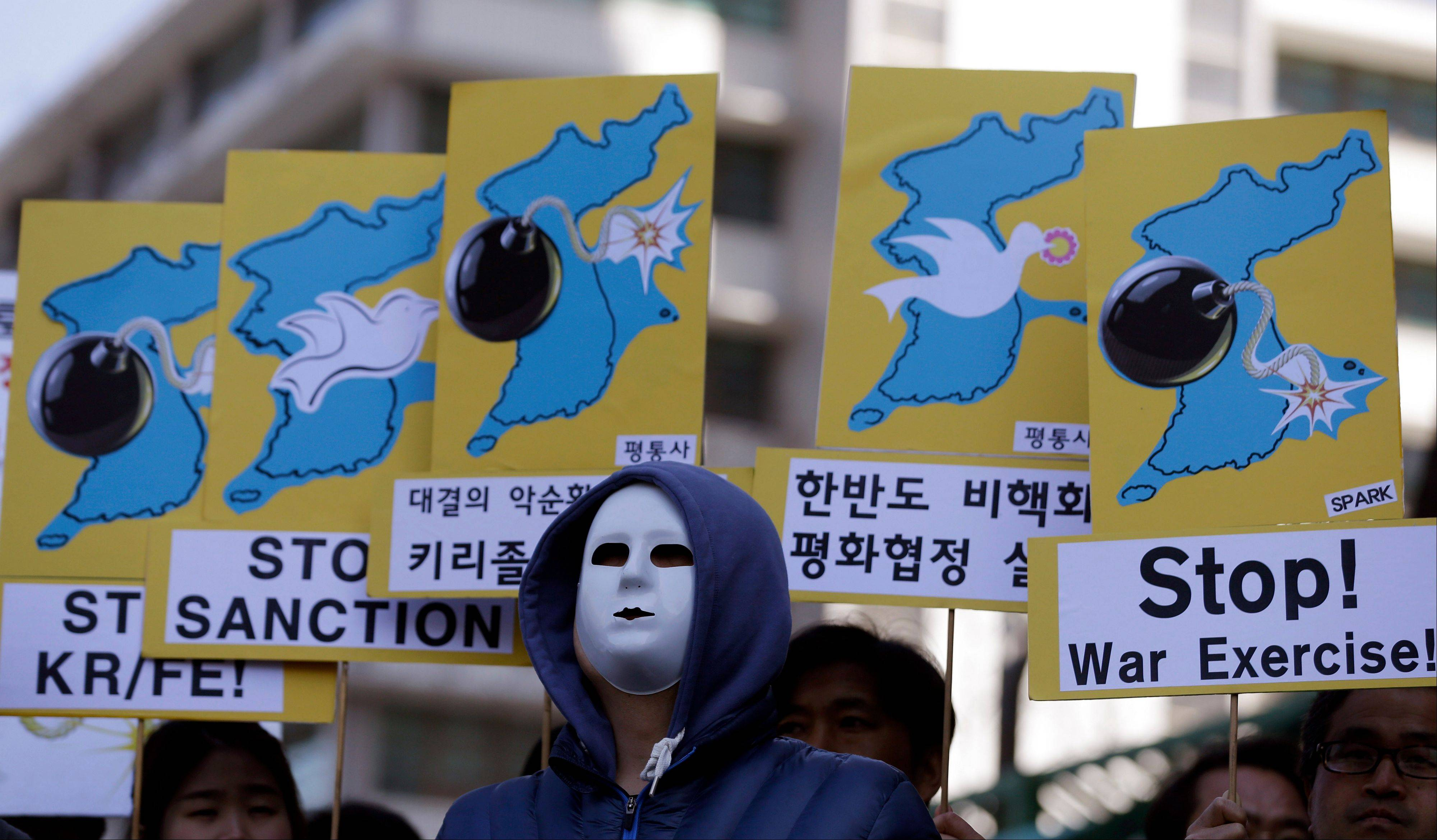 South Korean protesters wearing masks hold placards during a rally denouncing the annual joint military exercises, dubbed Key Resolve and Foal Eagle, between South Korea and the U.S., near the U.S. Embassy in Seoul, South Korea, Monday.