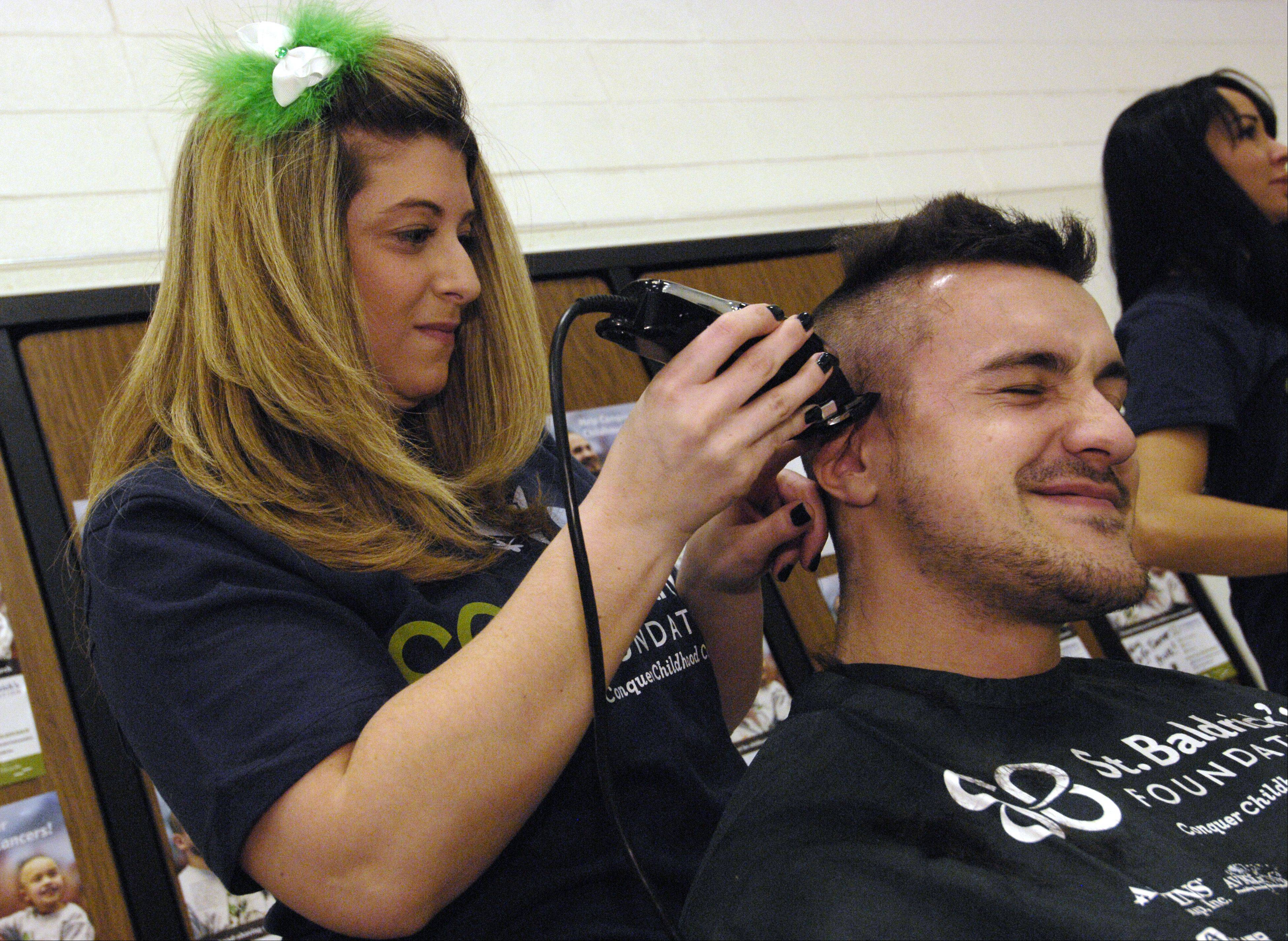 Gina Barzso of Bartlett shaves the head of Brandon Burck of Bartlett during the St. Baldrick's Day head shaving event at Evergreen Elementary School in honor of third grader Jack O'Donoghue, who's cancer is now in remission.