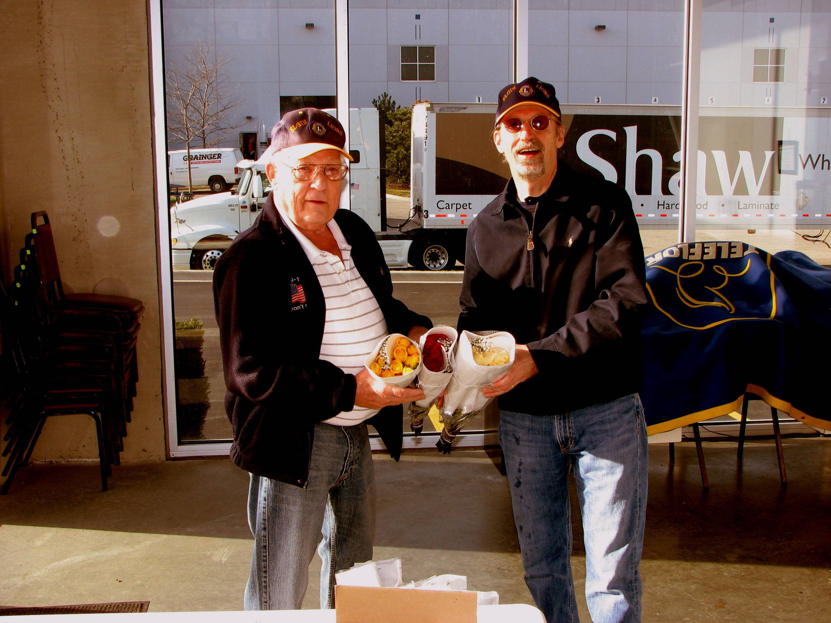 Elgin Lions Club members Chuck Merrell and Ed Bates show off roses to be delivered.