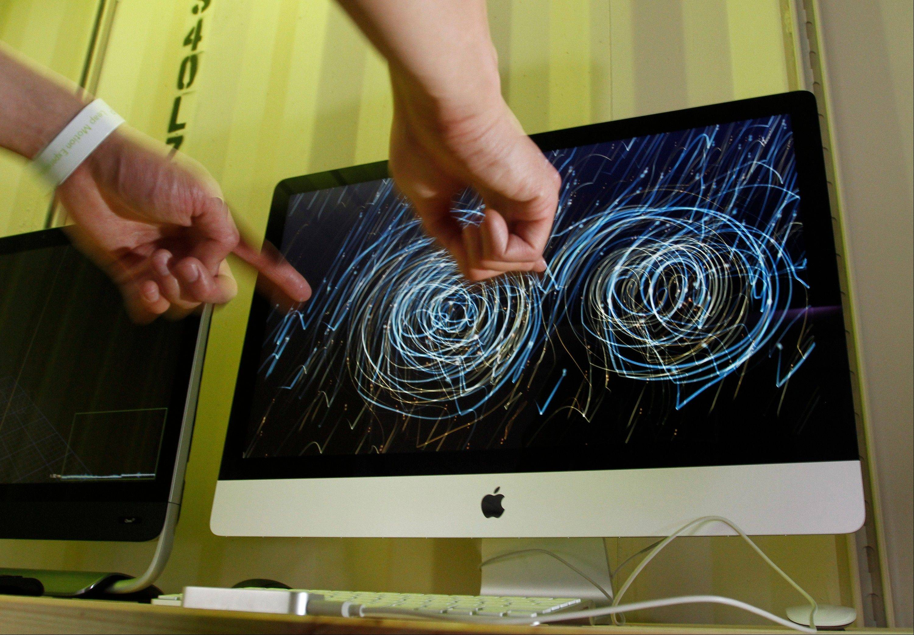 A SXSW Interactive Festival attendee samples LeapMotion's 3D motion control on Saturday, March 9, 2013 in Austin, Texas. The flash drive-sized device utilizes only hand movement to control a computer.(AP Photo/Jack Plunkett)