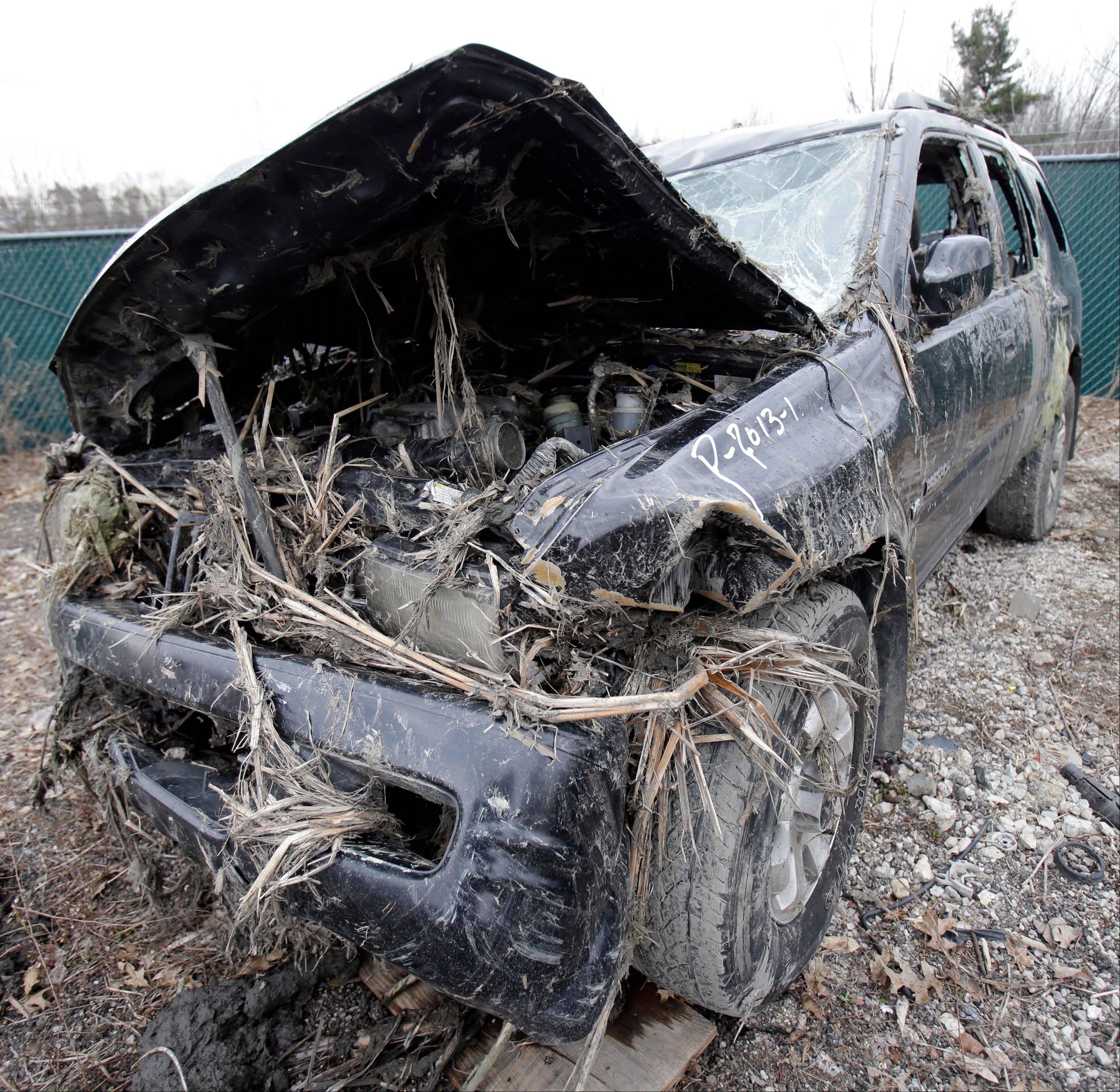 This Monday, March 11, 2013 photo in Southington, Ohio shows the vehicle where six people died in a crash early Sunday in Warren, Ohio. Two teens who escaped the crash that killed six friends in a swampy pond wriggled out of the wreckage by smashing a rear window and swimming away from the SUV, a state trooper said Monday.