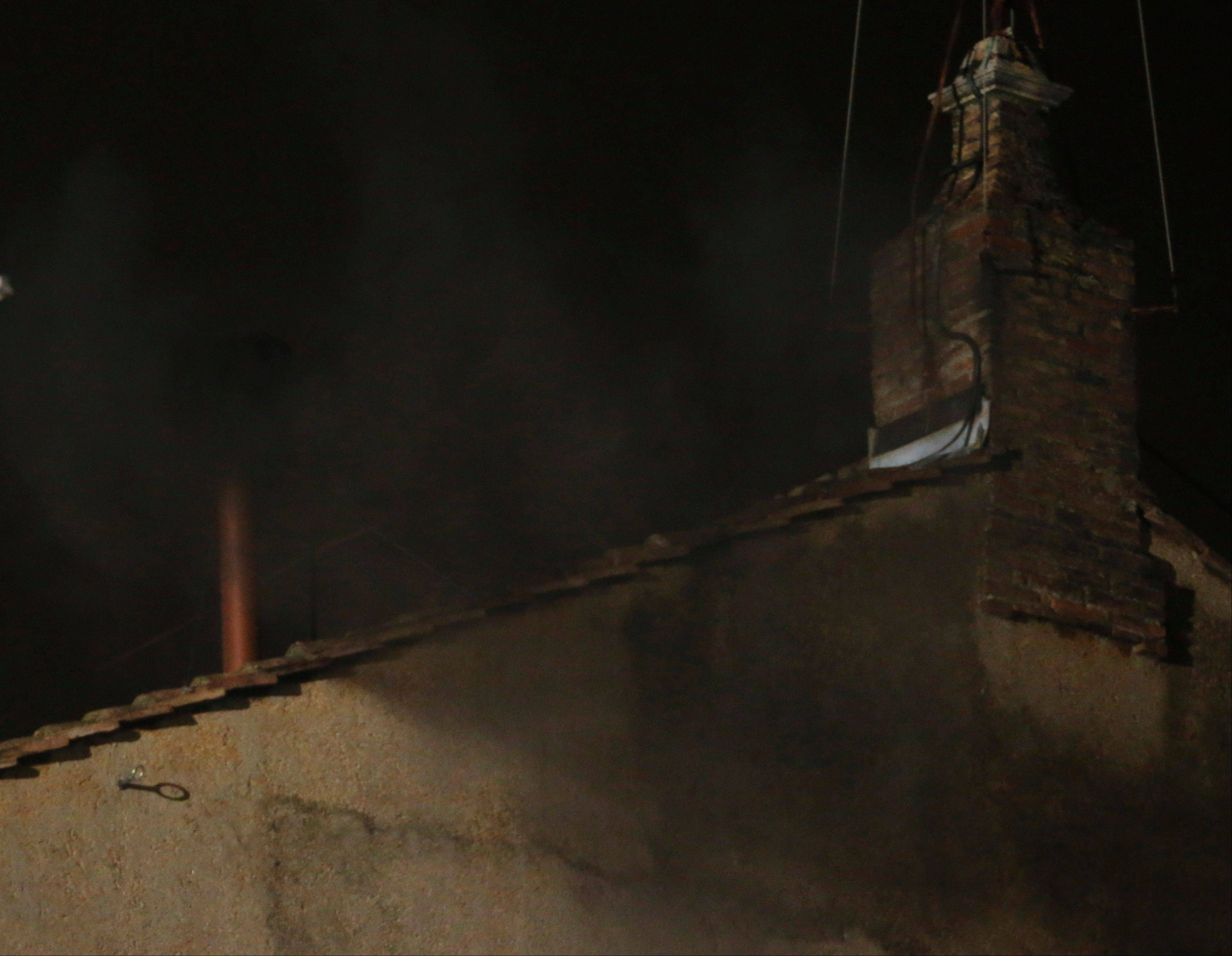 Black smoke emerges from the chimney on the roof of the Sistine Chapel, in St. Peter's Square at the Vatican, Tuesday, March 12, 2013. The black smoke indicates that the new pope has not been elected yet.