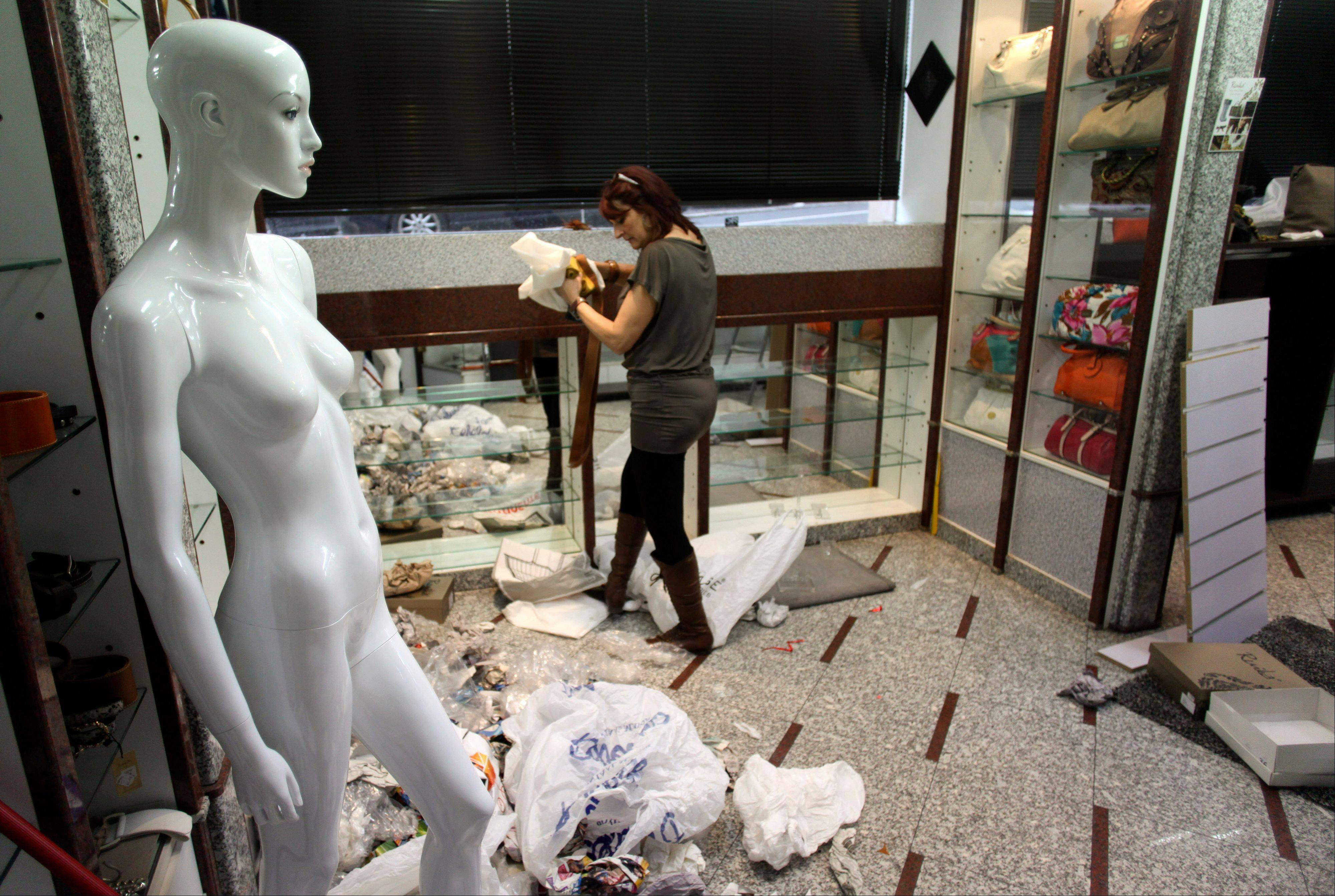 Sandra Alves dismantles her clothes and accessories store after closing it down due to the lack of customers, in Lisbon, Monday. Alves and her husband closed one of the two stores they owned after they weren't able to pay the rent and suppliers bills.