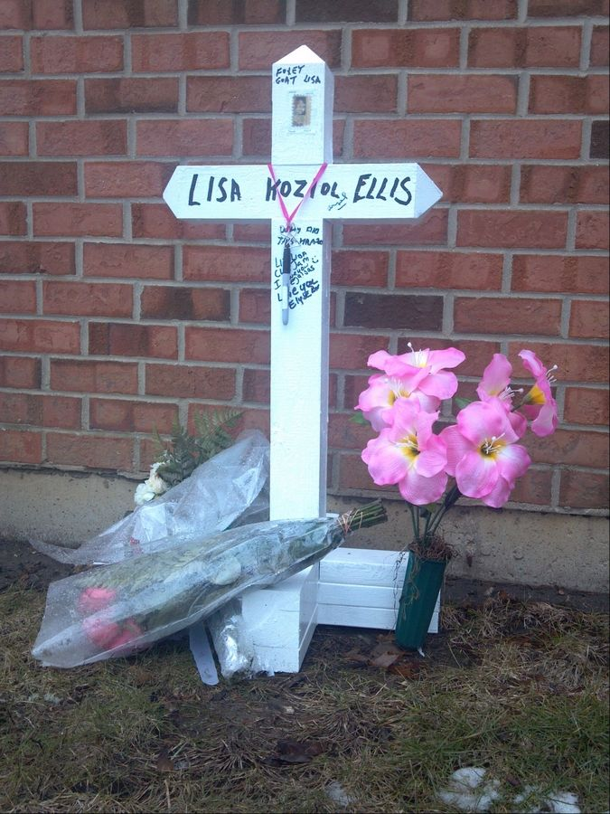 A white cross stands outside the Elgin home of Lisa Koziol-Ellis, who was found murdered March 2.