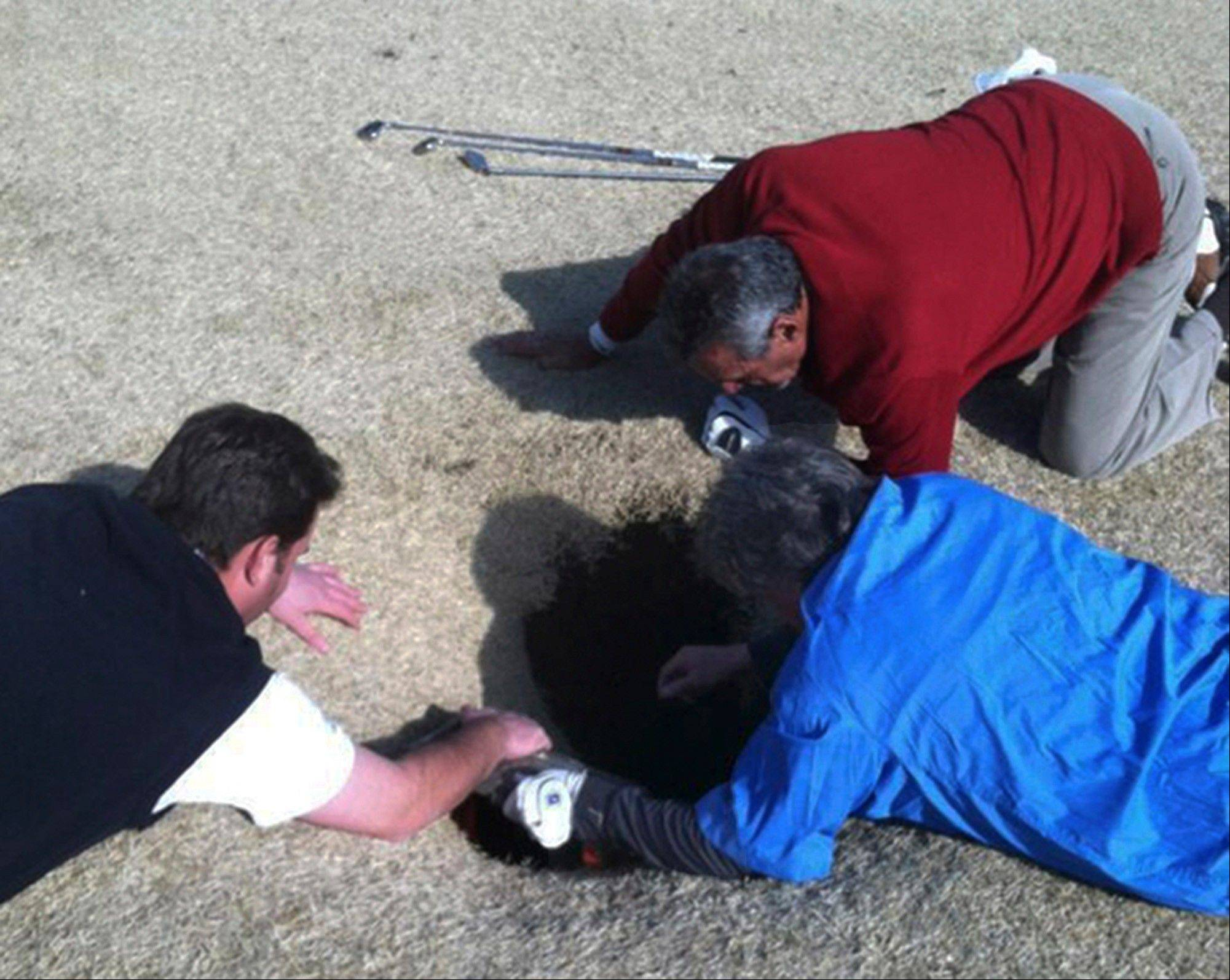 Hank Martinez, top, Ed Magaletta, right, and Russ Nobbe look into an 18-foot-deep and 10-foot-wide sinkhole that golfer Mark Minhal fell into while playing golf at the Annbriar Golf Course in Waterloo, Ill.