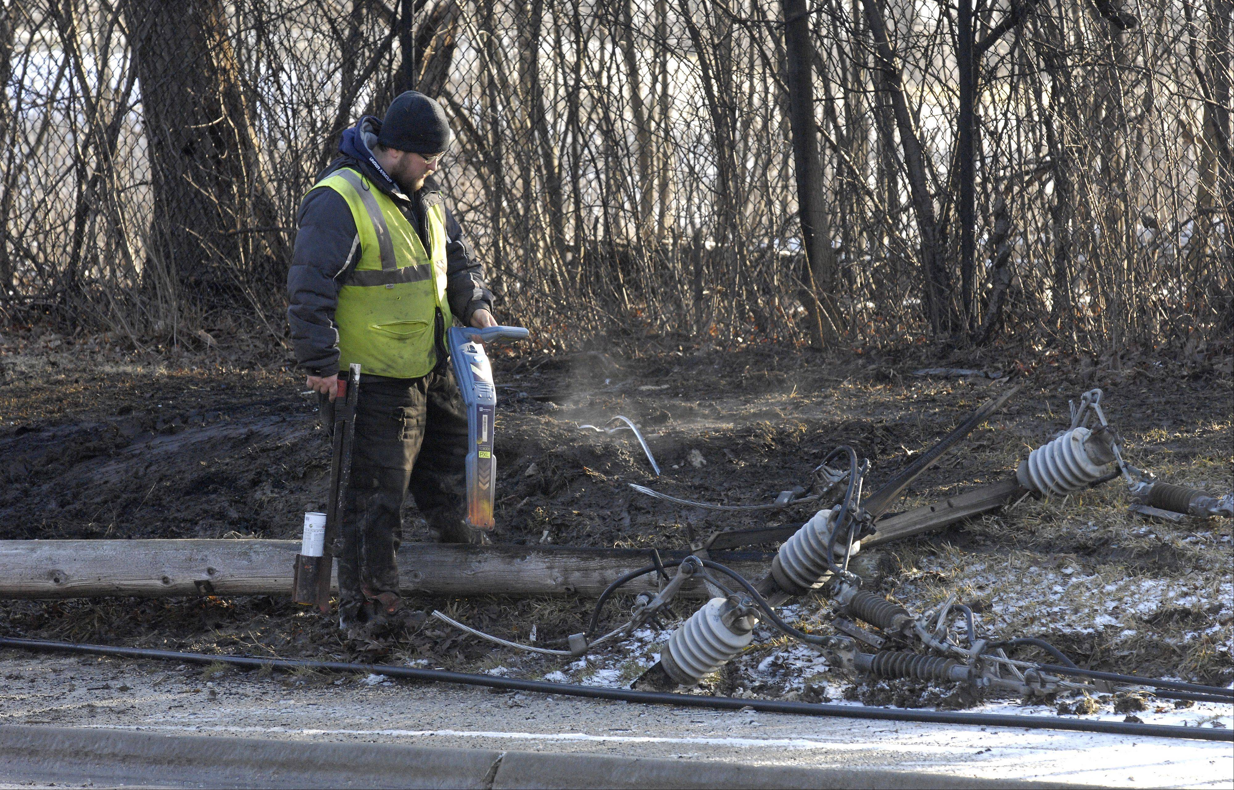 A worker starts preparation for repair of a utility pole that was knocked down during an early-morning Tuesday crash along Winfield Road, south of Roosevelt Road near Winfield. The vehicle involved was engulfed in flames.