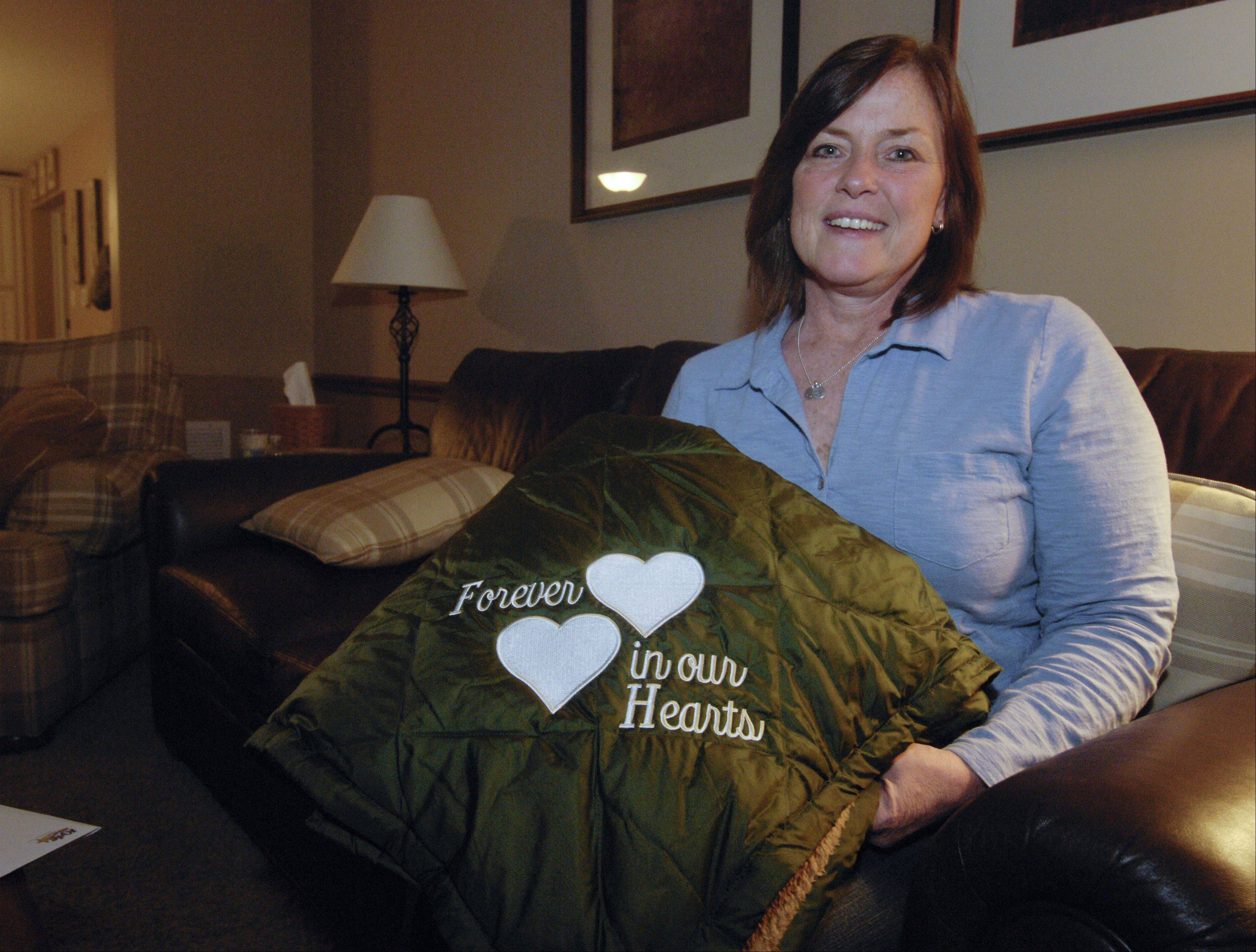 "Jill Zuleg of Naperville shows one of the blankets that the Kyle Zuleg Foundation gives to families going through the process of donating the organs of a loved one. Inspired by her own family's experience after the death of their teenage son Kyle, the blankets read ""Forever in our Hearts."""