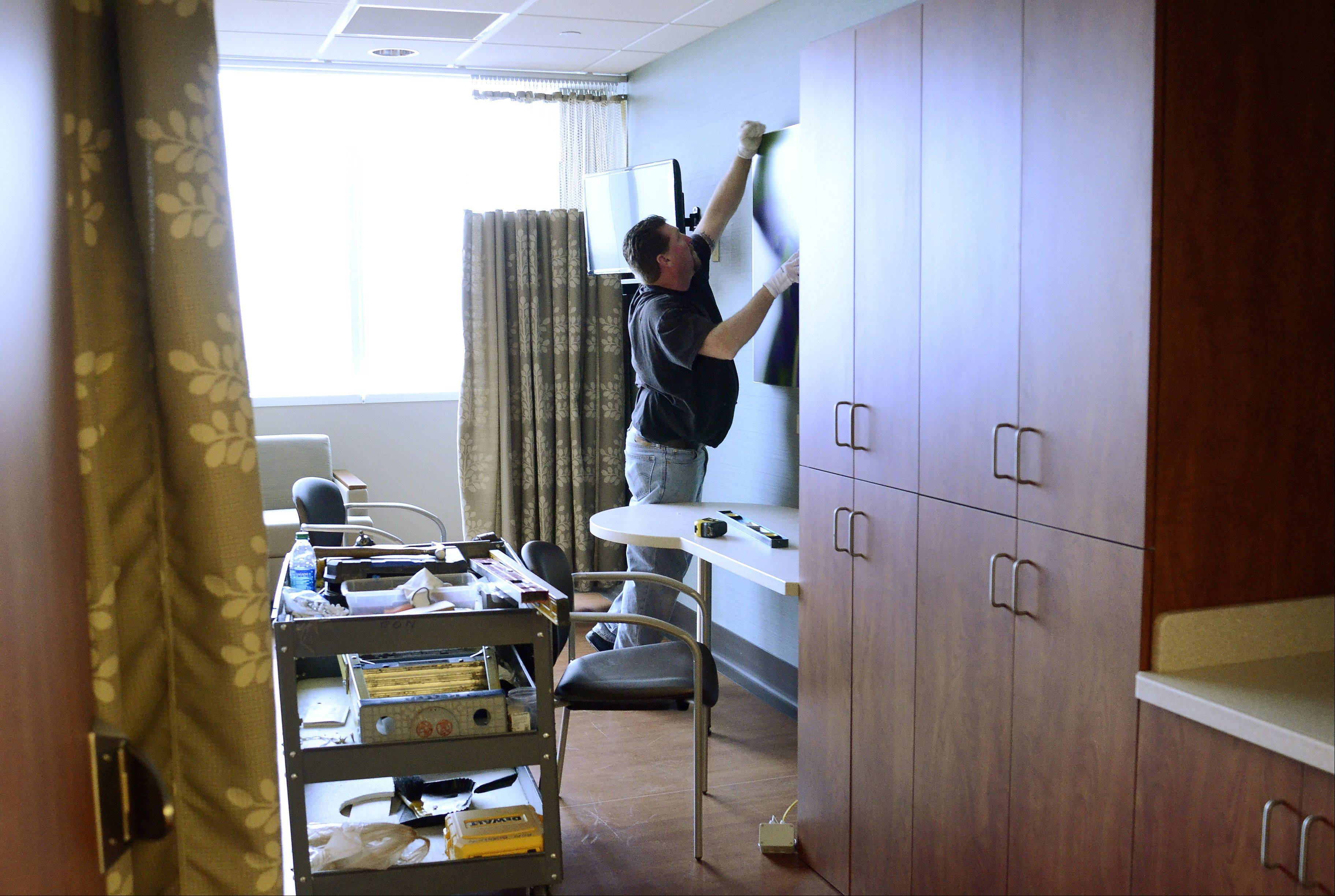 Ron Burklow hangs artwork in a patient's room.