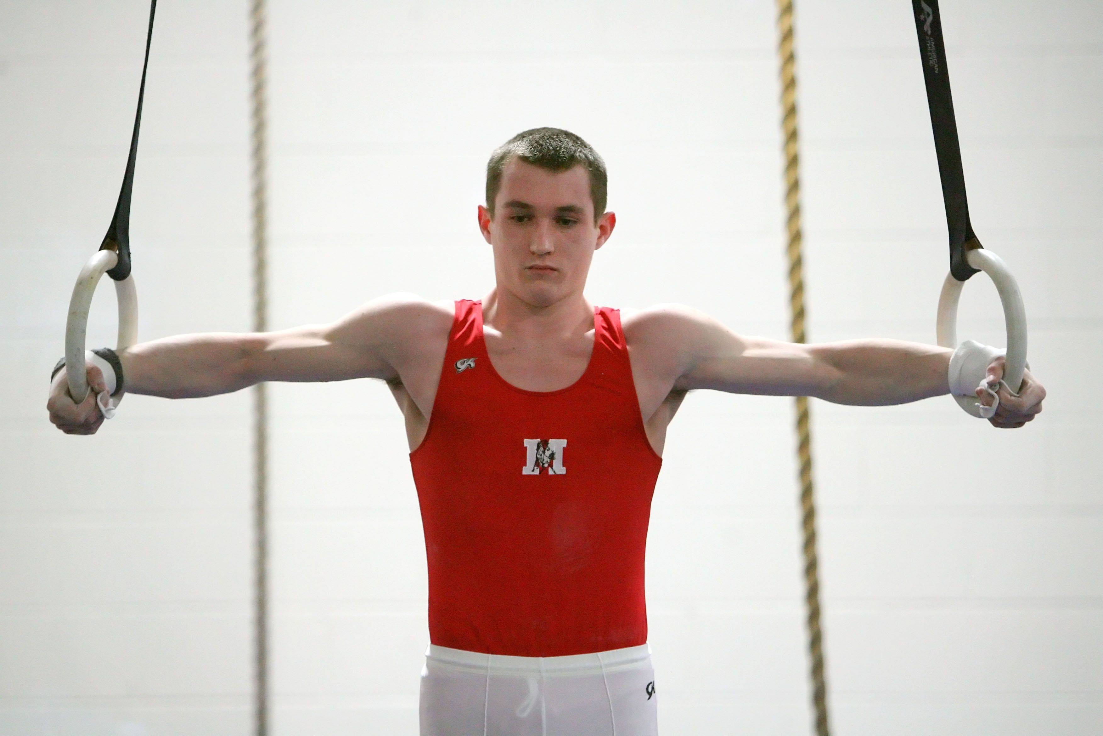 Mundelein's Cameron Mueller competes on still rings Tuesday at Libertyville.