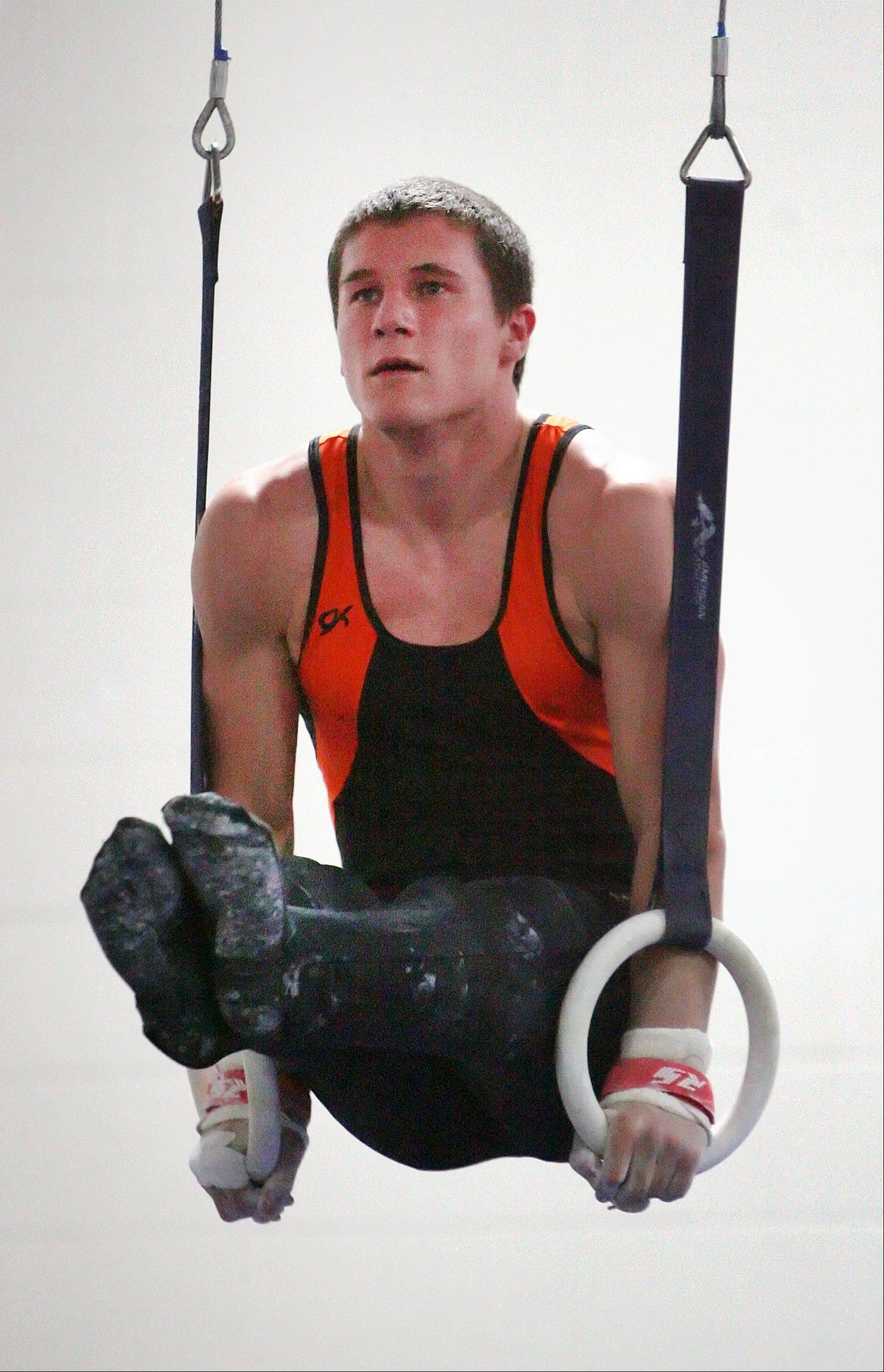 Libertyville's Jack Burke competes on still rings against Mundelein on Tuesday at Libertyville.