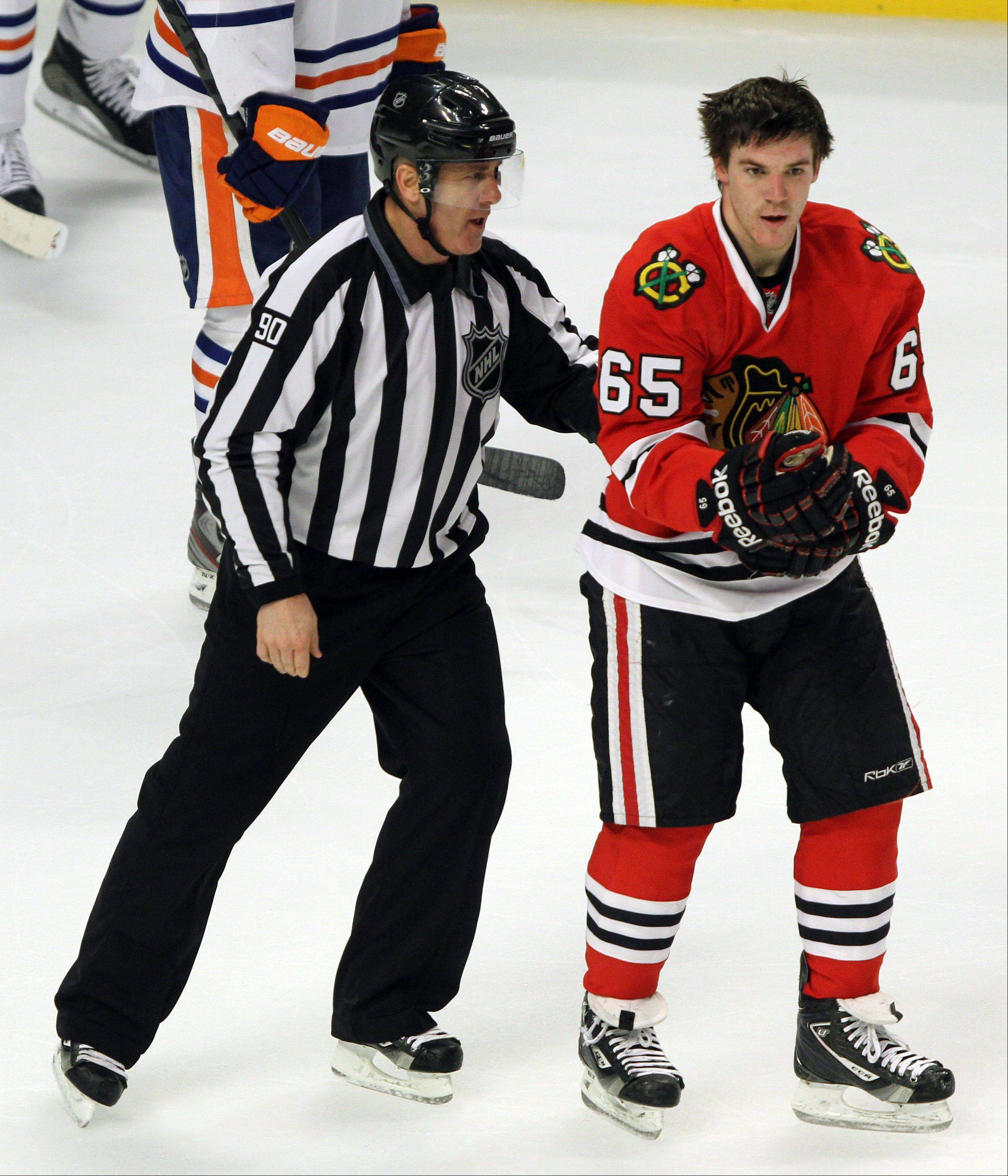 Steve Lundy/slundy@dailyherald.comNHL linesman Andy McElman leads Chicago Blackhawks center Andrew Shaw to the penalty box during their game against the Edmonton Oilers. McElman was hit in the face by a puck and suffered a serious injury. He's back working now. McElman is a native of Palatine.
