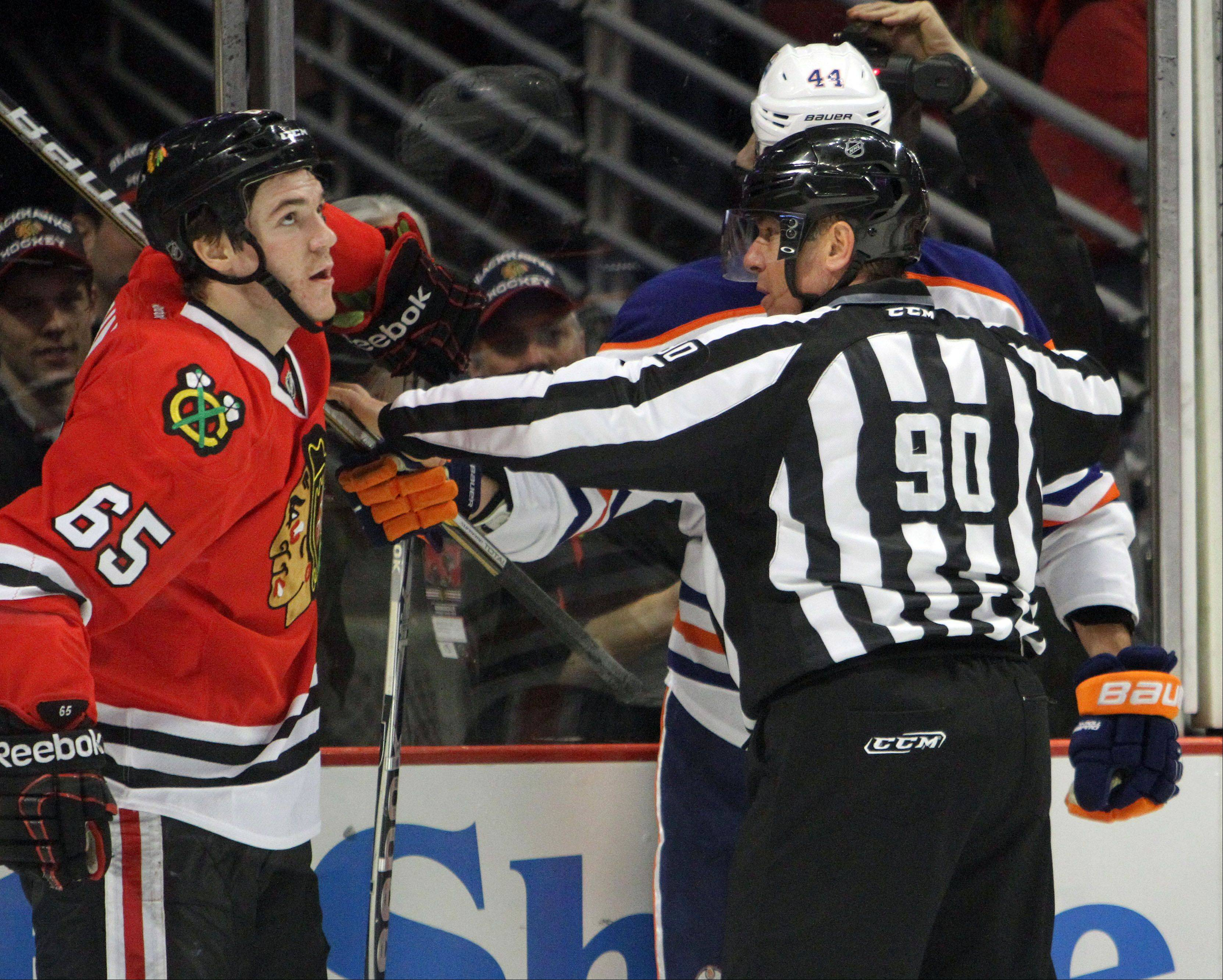 Steve Lundy/slundy@dailyherald.comNHL linesman Andy McElman breaks up a fight with Chicago Blackhawks center Andrew Shaw during their game against the Edmonton Oilers. McElman was hit in the face by a puck and suffered a serious injury. He's back working now. McElman is a native of Palatine.