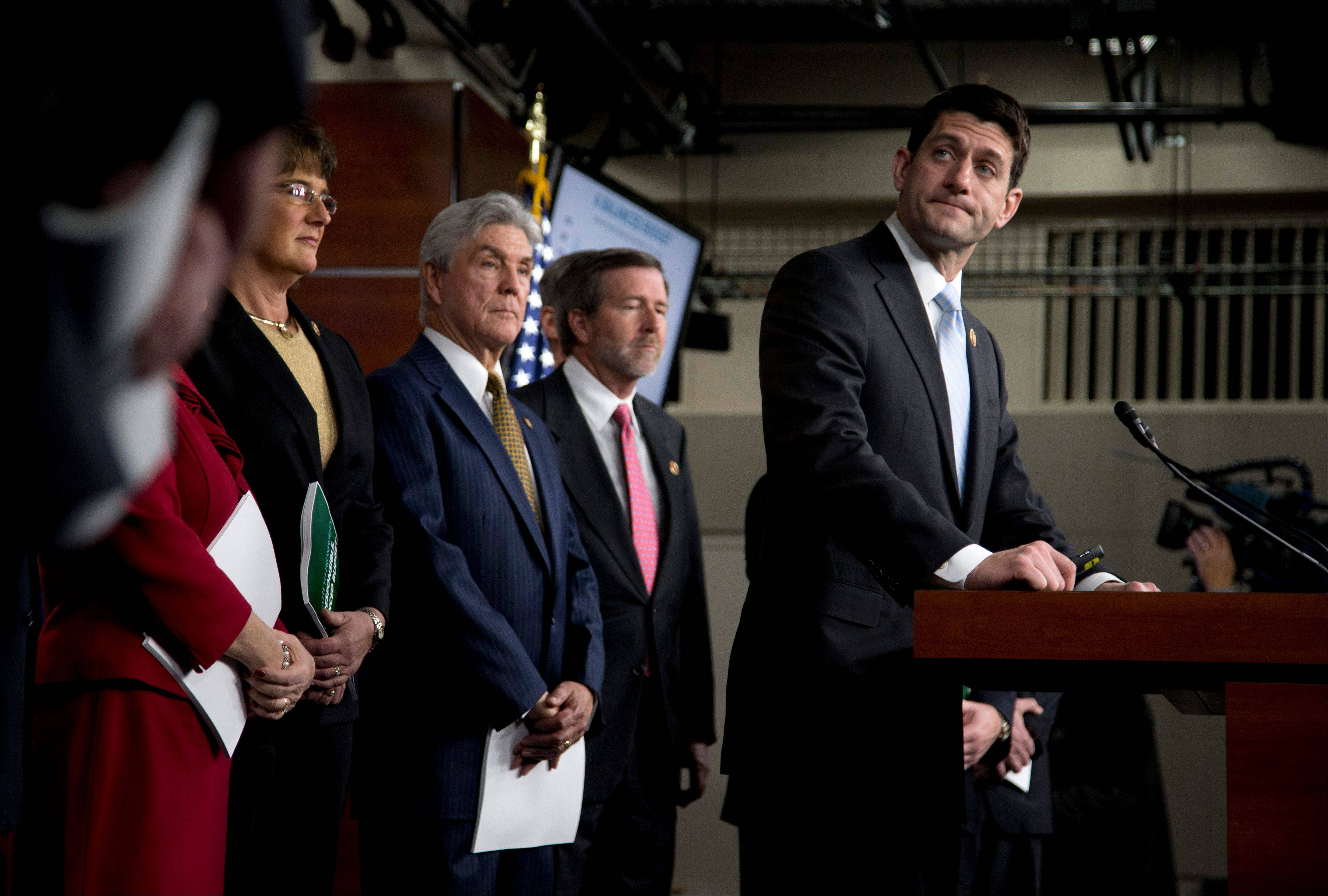 House Budget Committee Chairman Rep. Paul Ryan, R-Wis., right, pauses during a news conference on Capitol Hill in Washington, Tuesday.