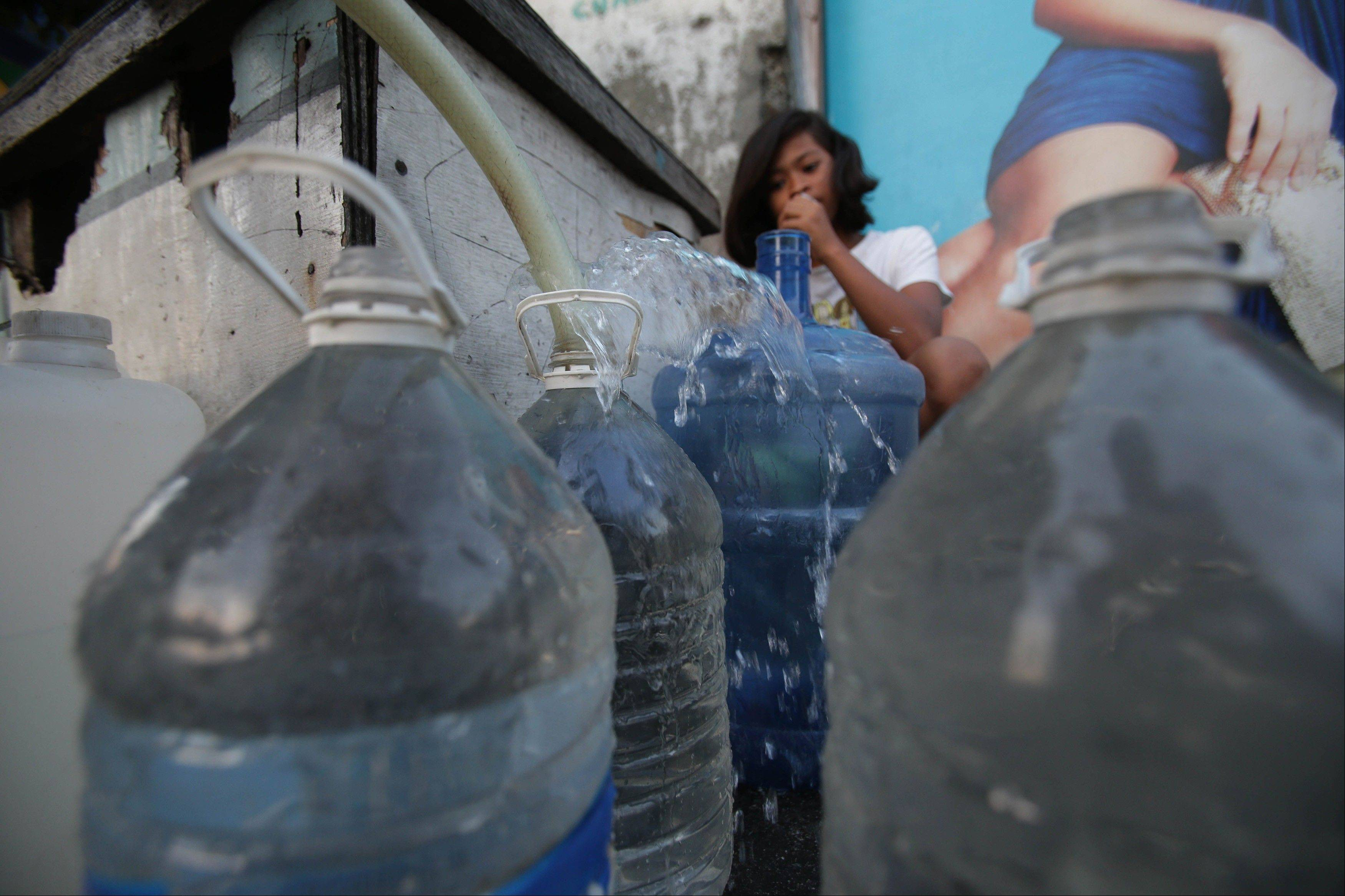 A Filipino girl watches at a makeshift water station in suburban Pasay, south of Manila, Philippines. Ninety-one percent of people living in Asia have improved access to clean water, a remarkable achievement over the last two decades in the world's most populous region.