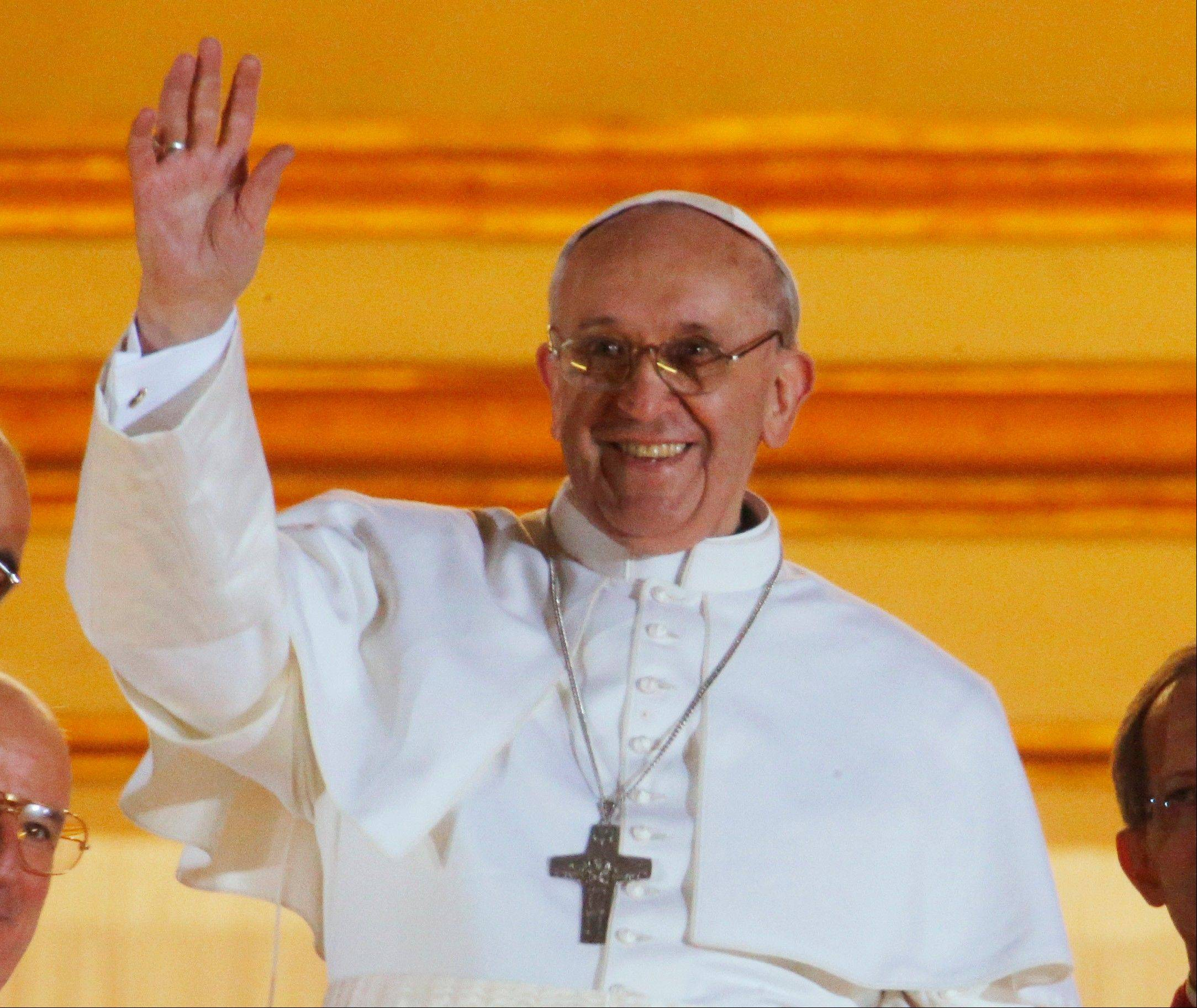Pope Francis waves to the crowd Wednesday from the central balcony of St. Peter�s Basilica at the Vatican.