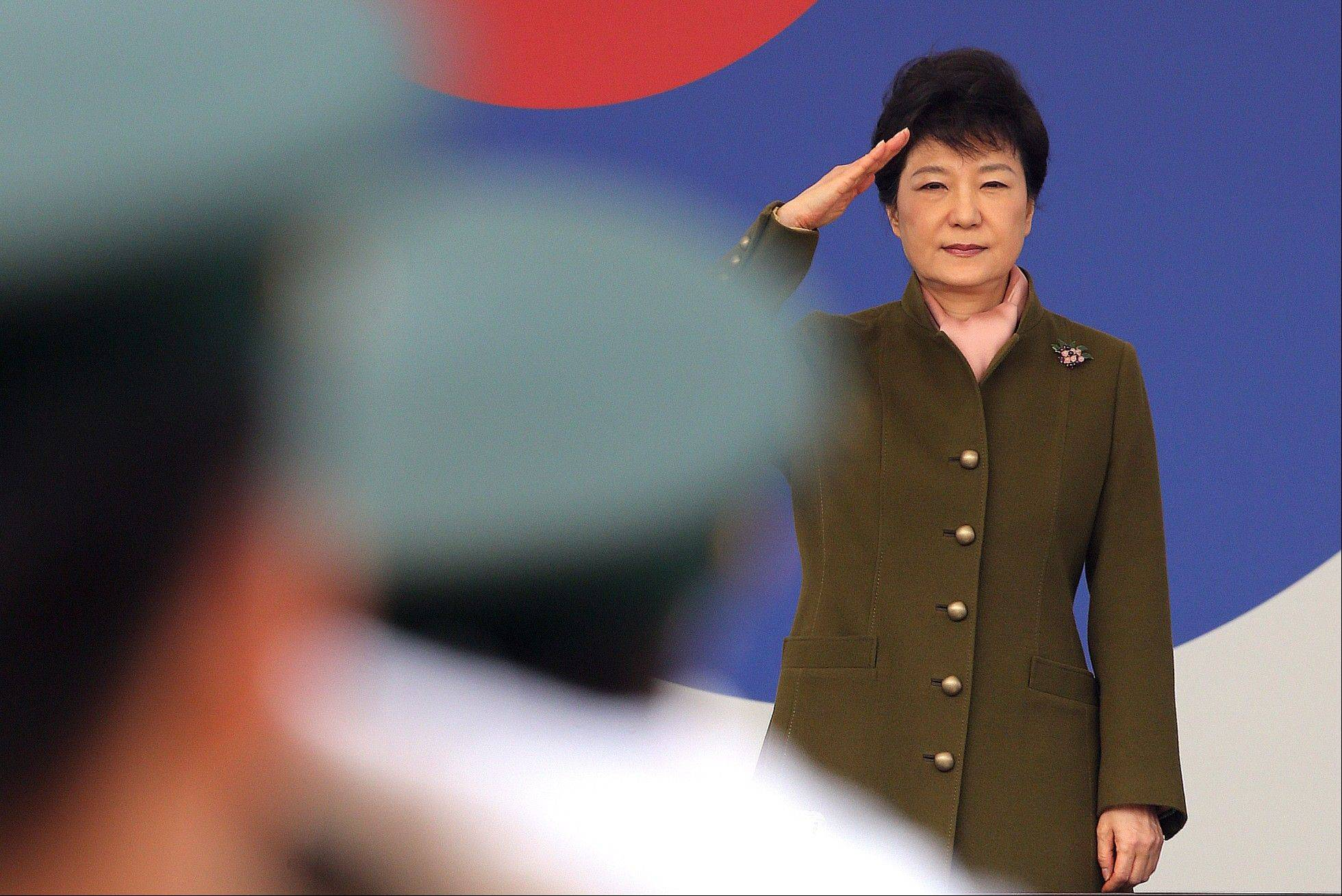 "South Korean President Park Geun-hye salutes during a joint commission ceremony of 5,780 new officers of Army, Navy, Air Force and Marines. The body that controls North Korea's military is dismissing the South Korea's new president with a sexist comment about the ""venomous swish"" of her skirt."