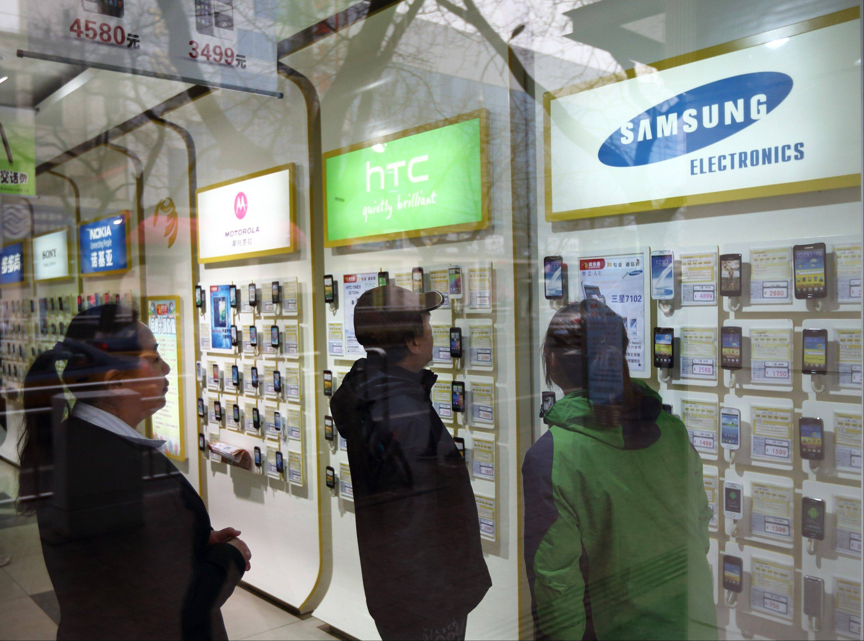 Customers look at Samsung Electronics Co. smartphones Tuesday at a China Mobile Ltd. store in Beijing.