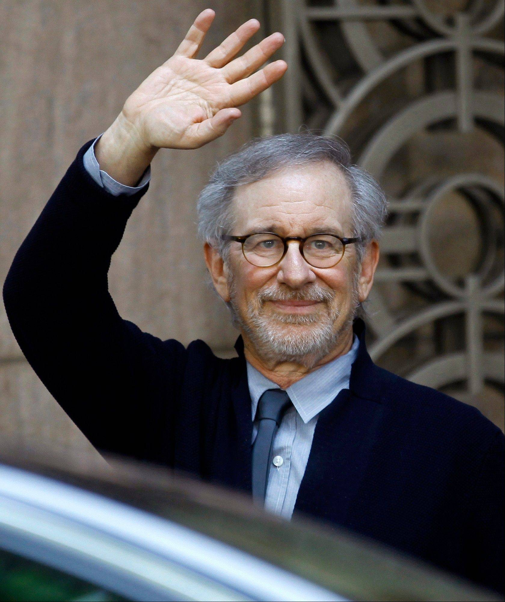 Director Steven Spielberg waves to the media as he leaves Indian Industrialist Anil Ambani's office in Mumbai, India.