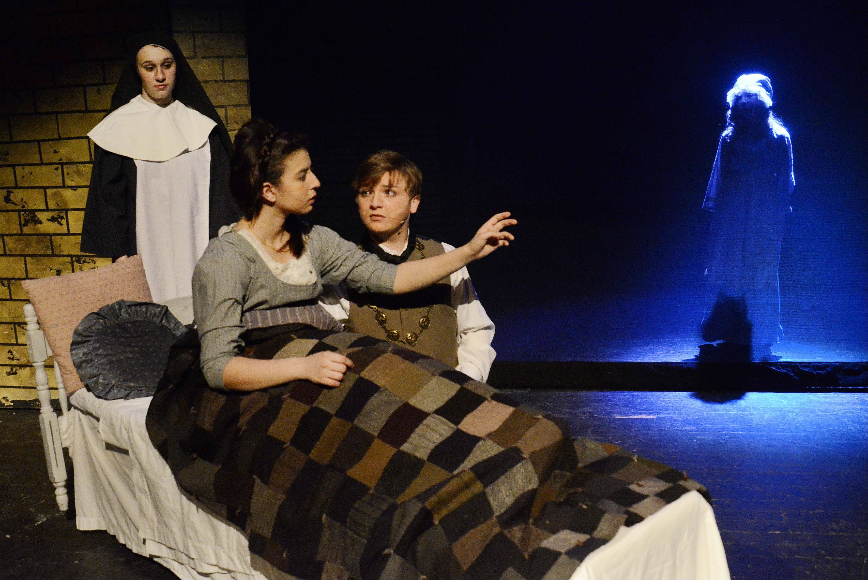 "From left, Grace Bellino plays a nun, Eliana Ford is Fantine, Brandon Pisano is Jean Valjean and Jaclyn Ryan is young Cosette in the Death of Fantine scene from the dress rehearsal for Streamwood High School's production of ""Les Miserables."""