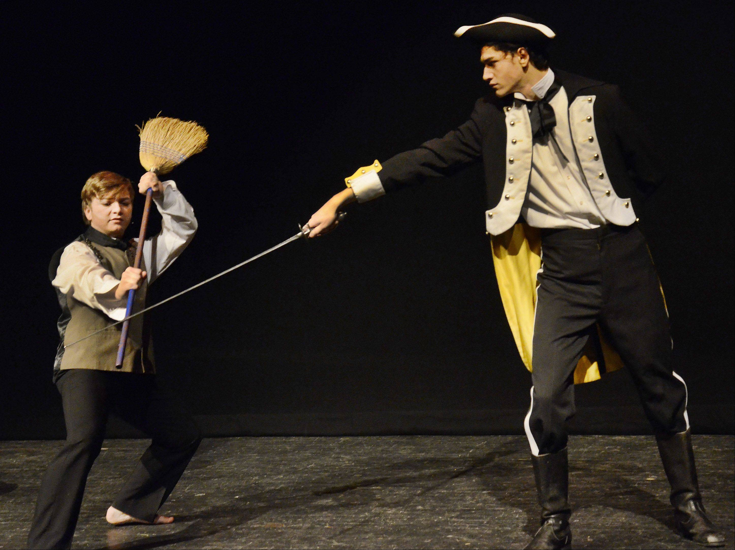"Jean Valjean played by Brandon Pisano, left, and Inspector Javert, played by Justis Olivarez, confront each other during a dress rehearsal for Streamwood High School's production of ""Les Miserables."""
