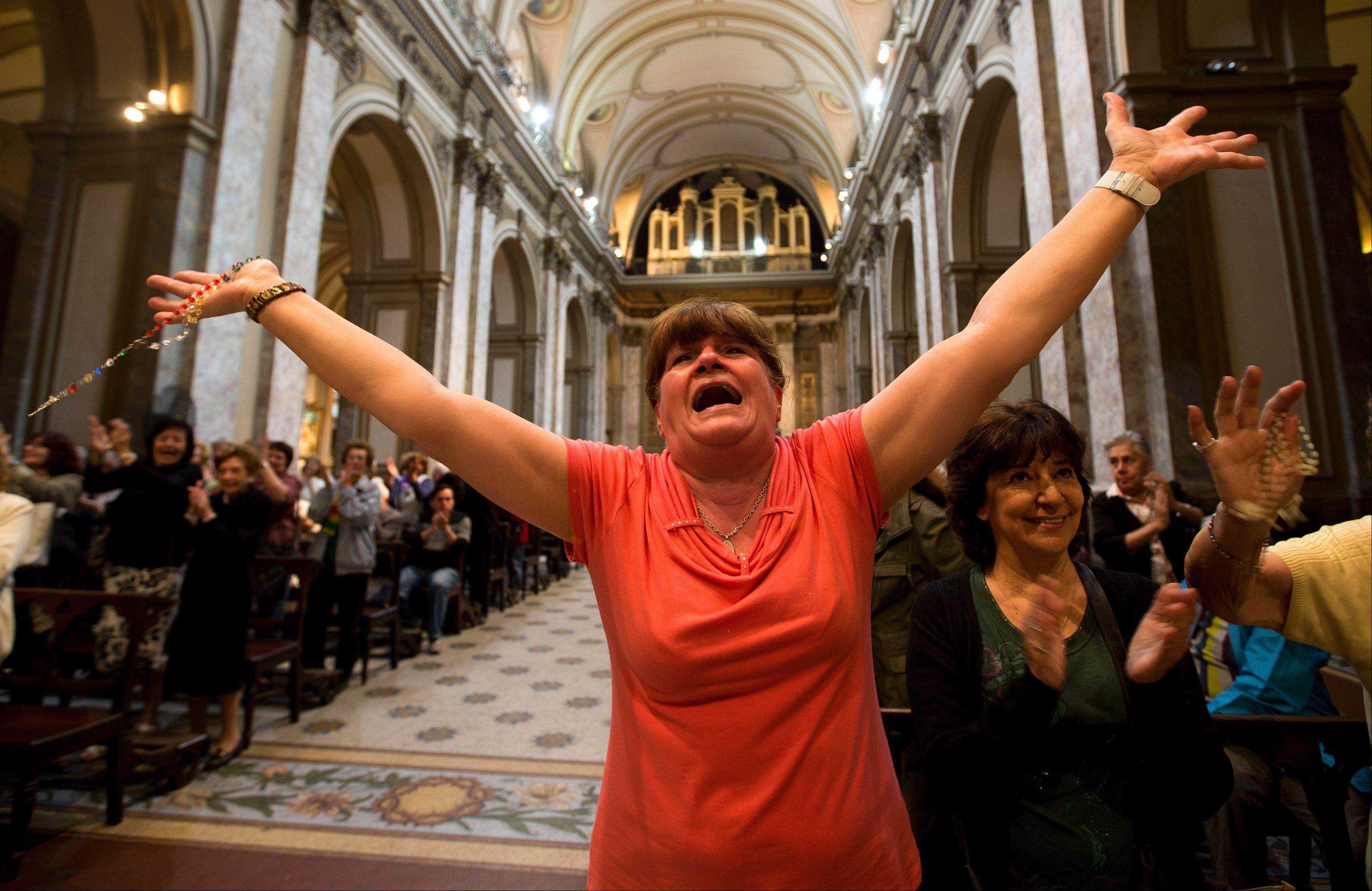 Paola La Rocca celebrates Wednesday after hearing on the speakers at the Metropolitan Cathedral that Buenos Aires' Archbishop Jorge Bergoglio was chosen as Pope in Buenos Aires, Argentina.