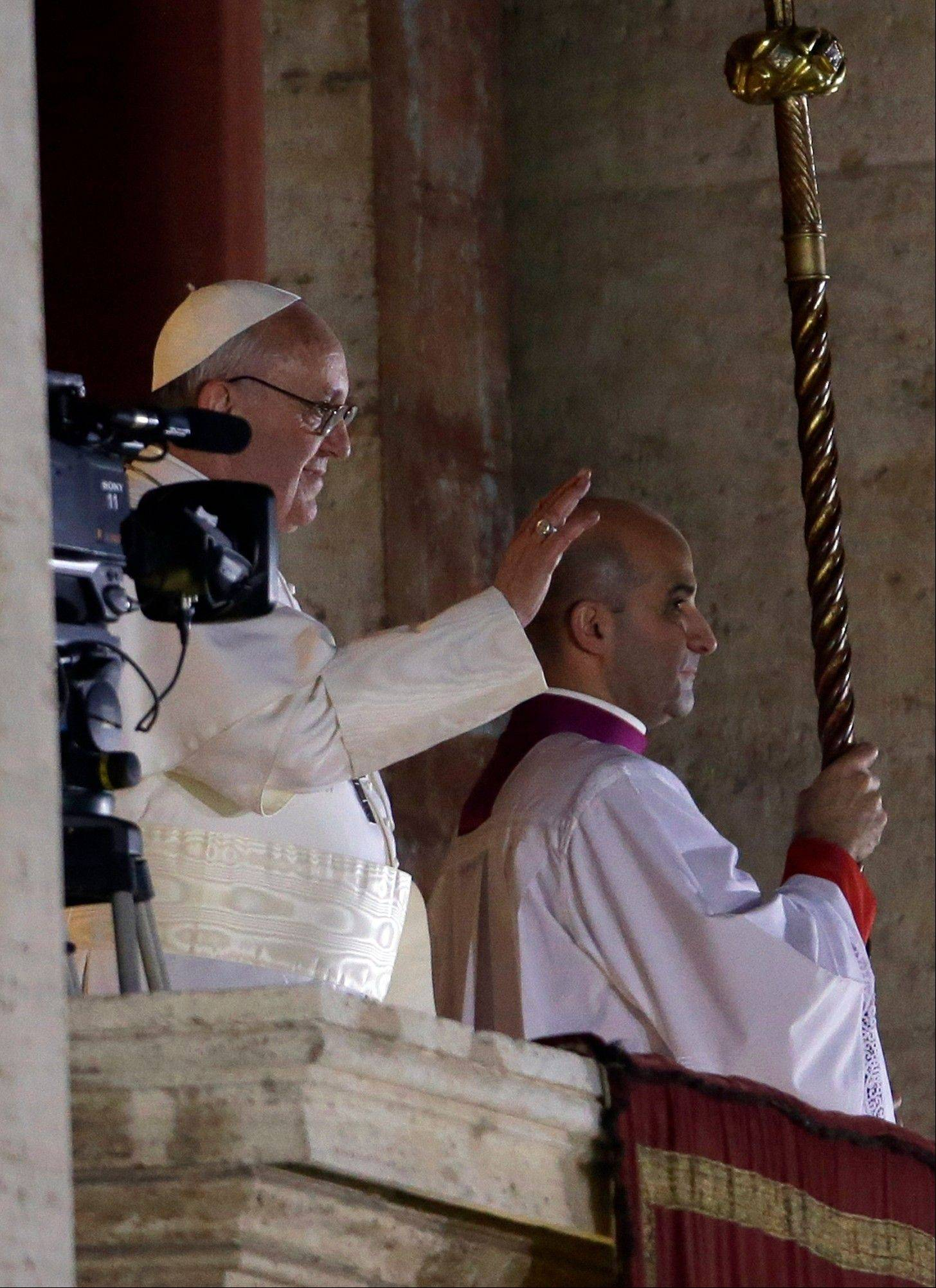 Pope Francis waves to the crowd from the central balcony of St. Peter's Basilica at the Vatican, Wednesday, March 13, 2013. Cardinal Jorge Bergoglio who chose the name of Francis is the 266th pontiff of the Roman Catholic Church.