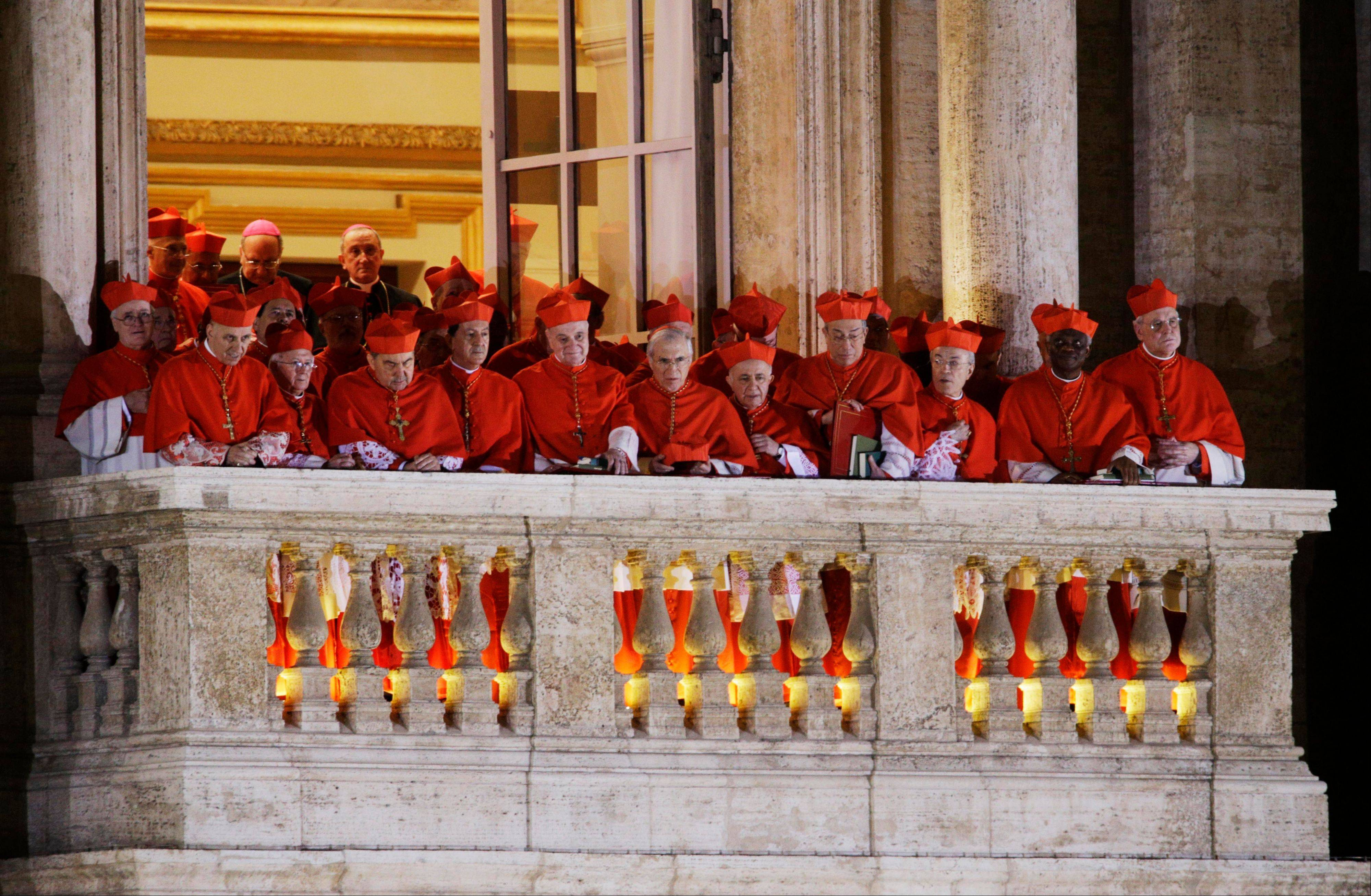 Cardinals watch as Pope Francis speaks to the crowd from the central balcony of St. Peter's Basilica at the Vatican, Wednesday, March 13, 2013. Cardinal Jorge Bergoglio, who chose the name of Francis, is the 266th pontiff of the Roman Catholic Church.