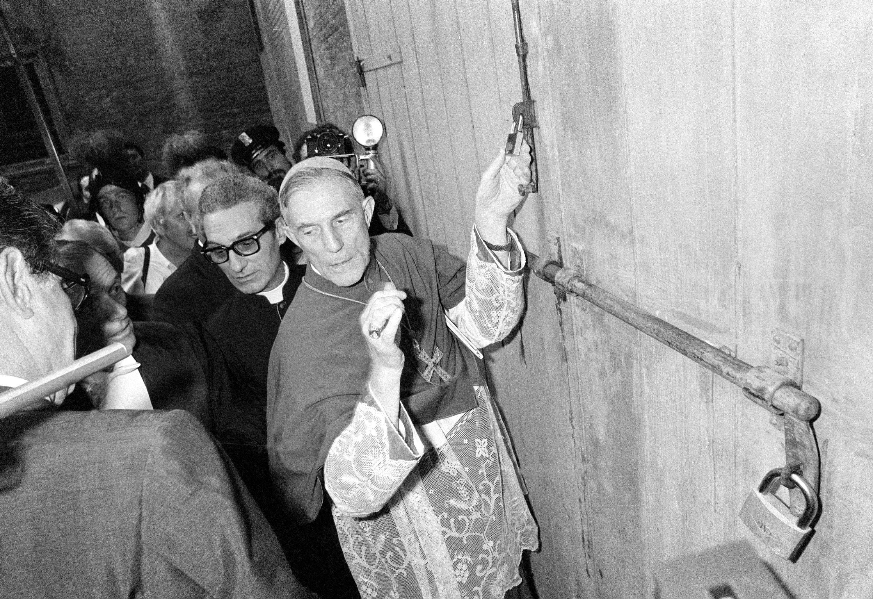 This Aug. 25, 1978 file photo shows Bishop Jacques Martin of France, center, outgoing head of the Pontifical household, and Guglielmo Felice, consistorial lawyer of Vatican City, left, locking one of the gates of the conclave area after all 111 cardinals entered the conclave to elect a new pope. Elaborate ritual and veils of secrecy, after all, are fundamental to the papal mystique, seen as the glue the binds worshippers in faith.