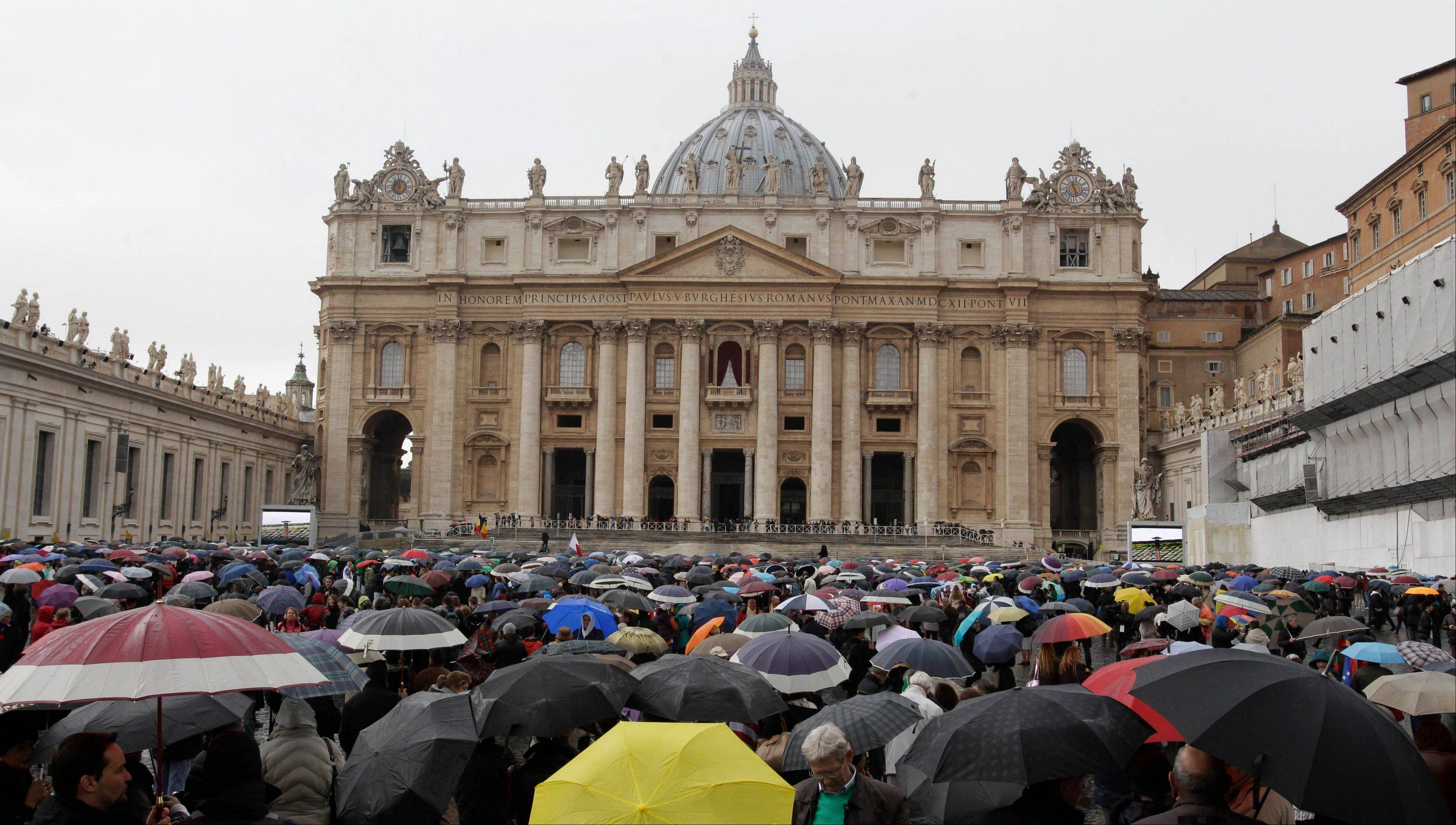 Crowds gather Wednesday in front of St. Peter's Basilica in St. Peter's Square as they wait for smoke from the Sistine Chapel during the second day of the conclave to elect a new pope at the Vatican.