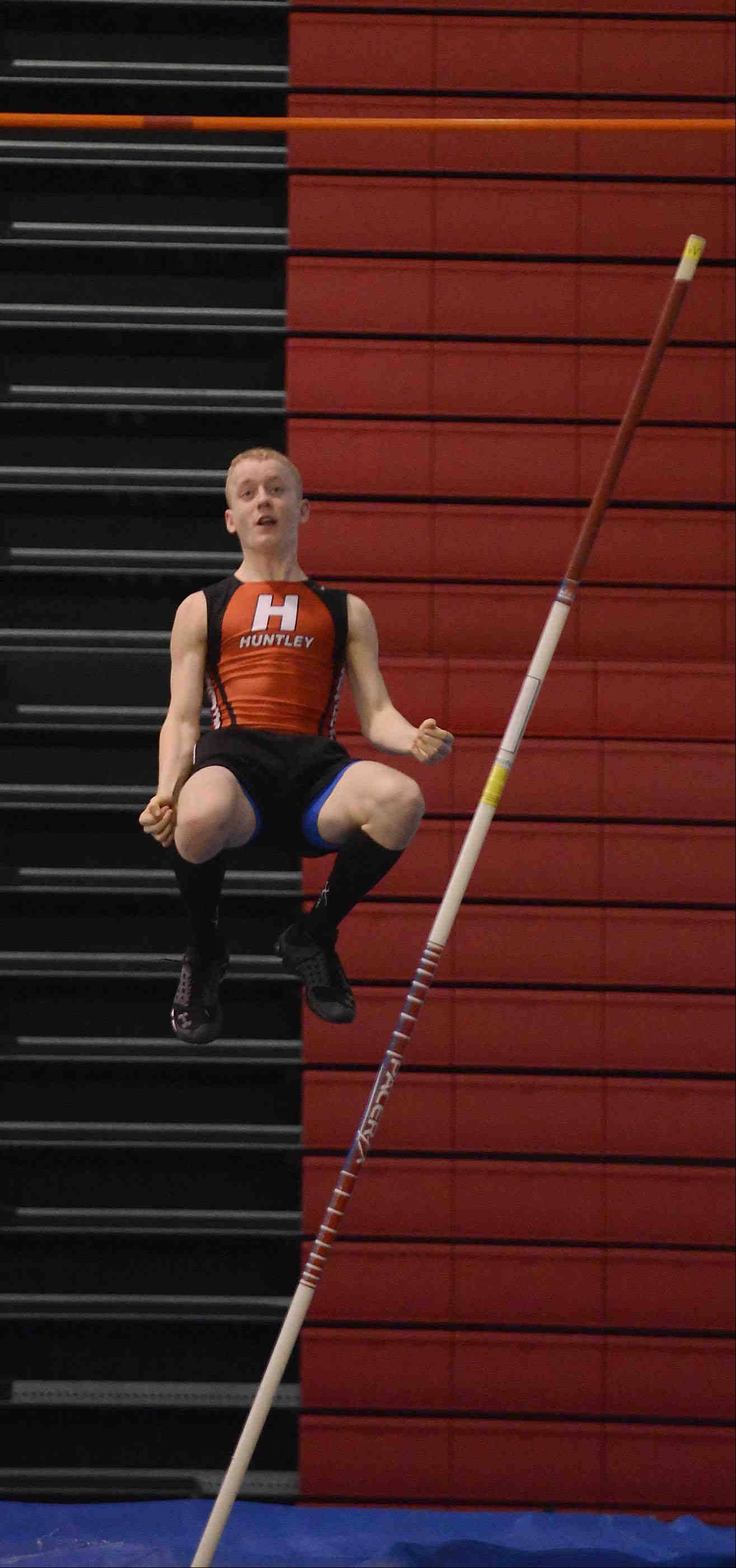 Huntley's Craig Lambert falls to the mat after clearing the bar in the pole vault Wednesday at the Fox Valley Conference indoor meet at Dundee-Crown. He finished third.
