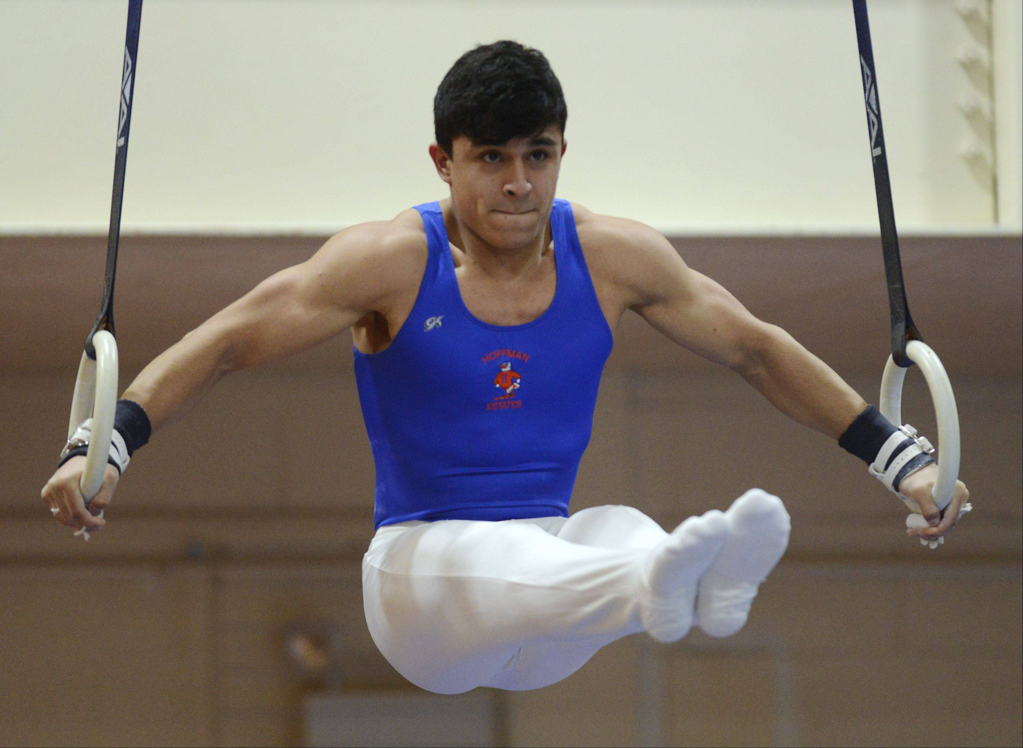 Hoffman Estates' Jake Santiago competes on the still rings during Wednesday's boys gymnastics triangular meet at Schaumburg.