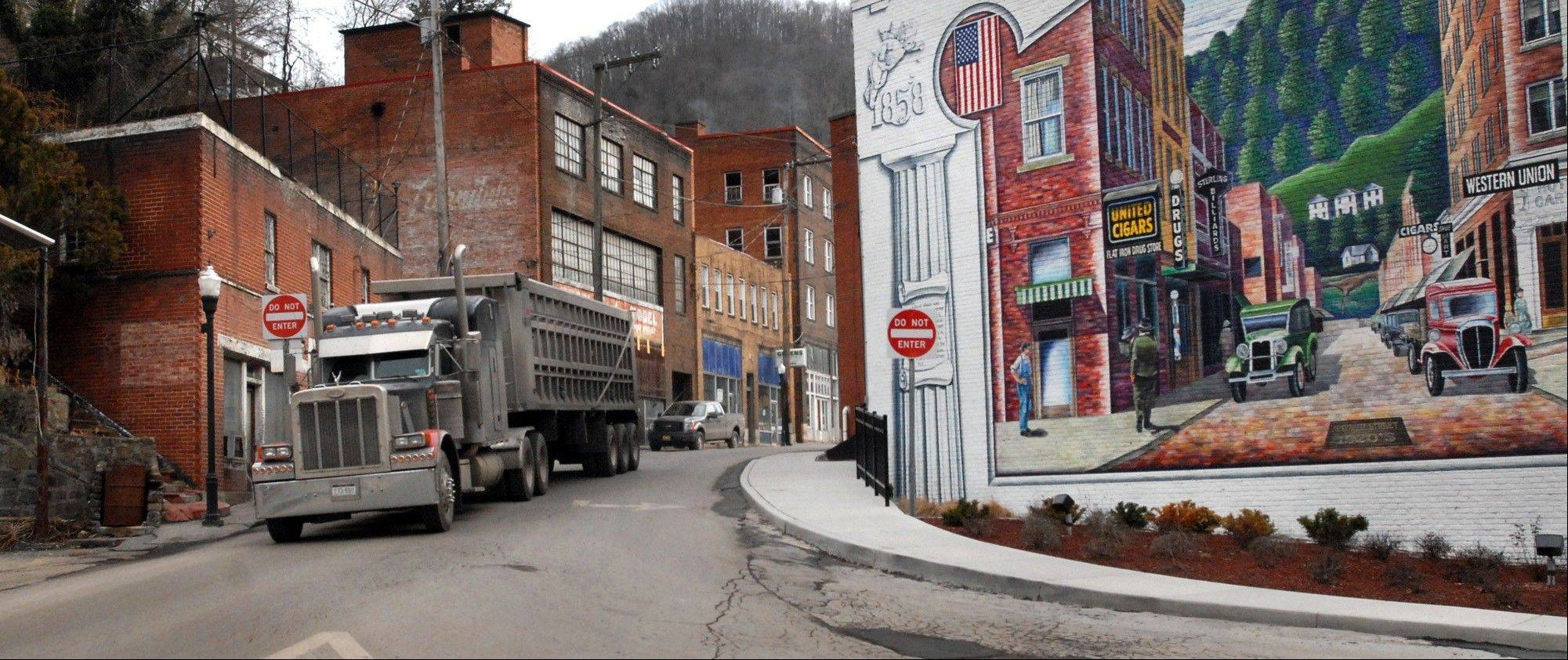 A coal truck drives out of downtown Welch, W.Va. A record number of U.S. counties _ more than 1 in 3 _ are now dying off, hit by an aging population and weakened local economies that are spurring young adults to seek jobs elsewhere.