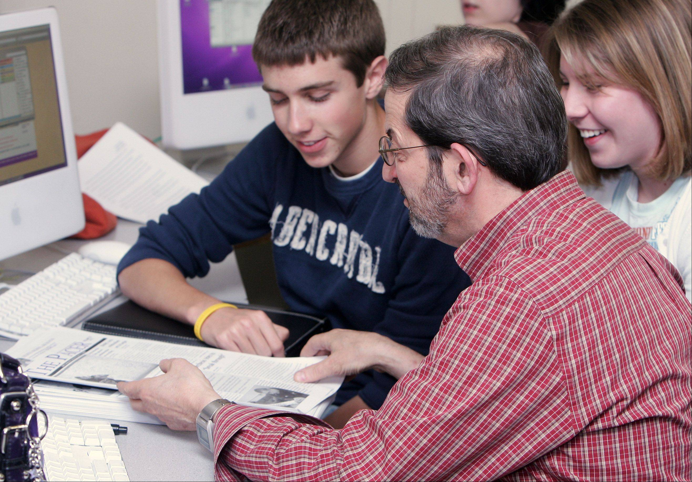 Adviser Stan Zoller works with members of the Rolling Meadows High School student newspaper, The Pacer, prepare the next issue. Zoller recently learned he will not have a job at the high school next year.