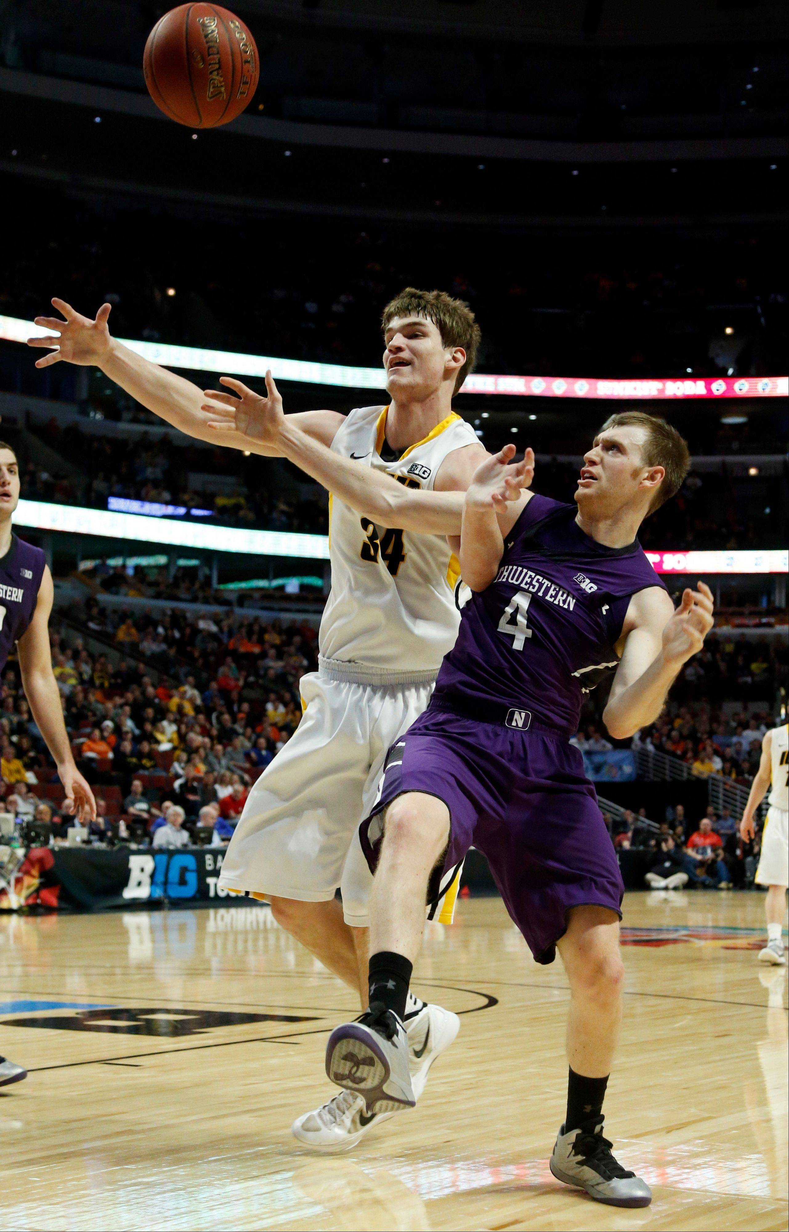 Iowa's Adam Woodbury (34) and Northwestern's Alex Marcotullio (4) battle for a loose ball during the first half of an NCAA college basketball game at the Big Ten tournament Thursday, March 14, 2013, in Chicago. (AP Photo/Charles Rex Arbogast)