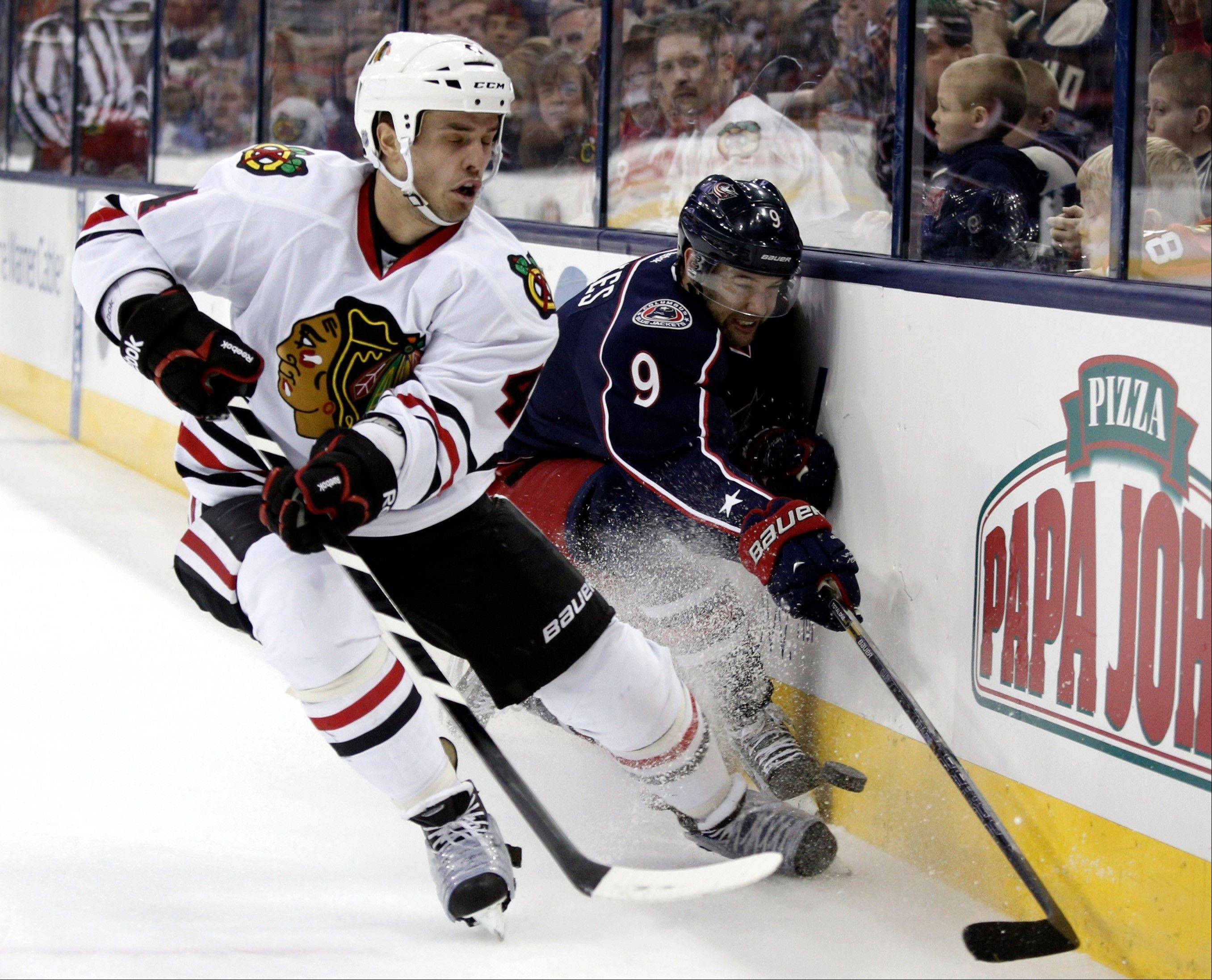 Chicago Blackhawks� Niklas Hjalmarsson, left, of Sweden works for the puck against Columbus Blue Jackets� Colton Gillies during the second period.