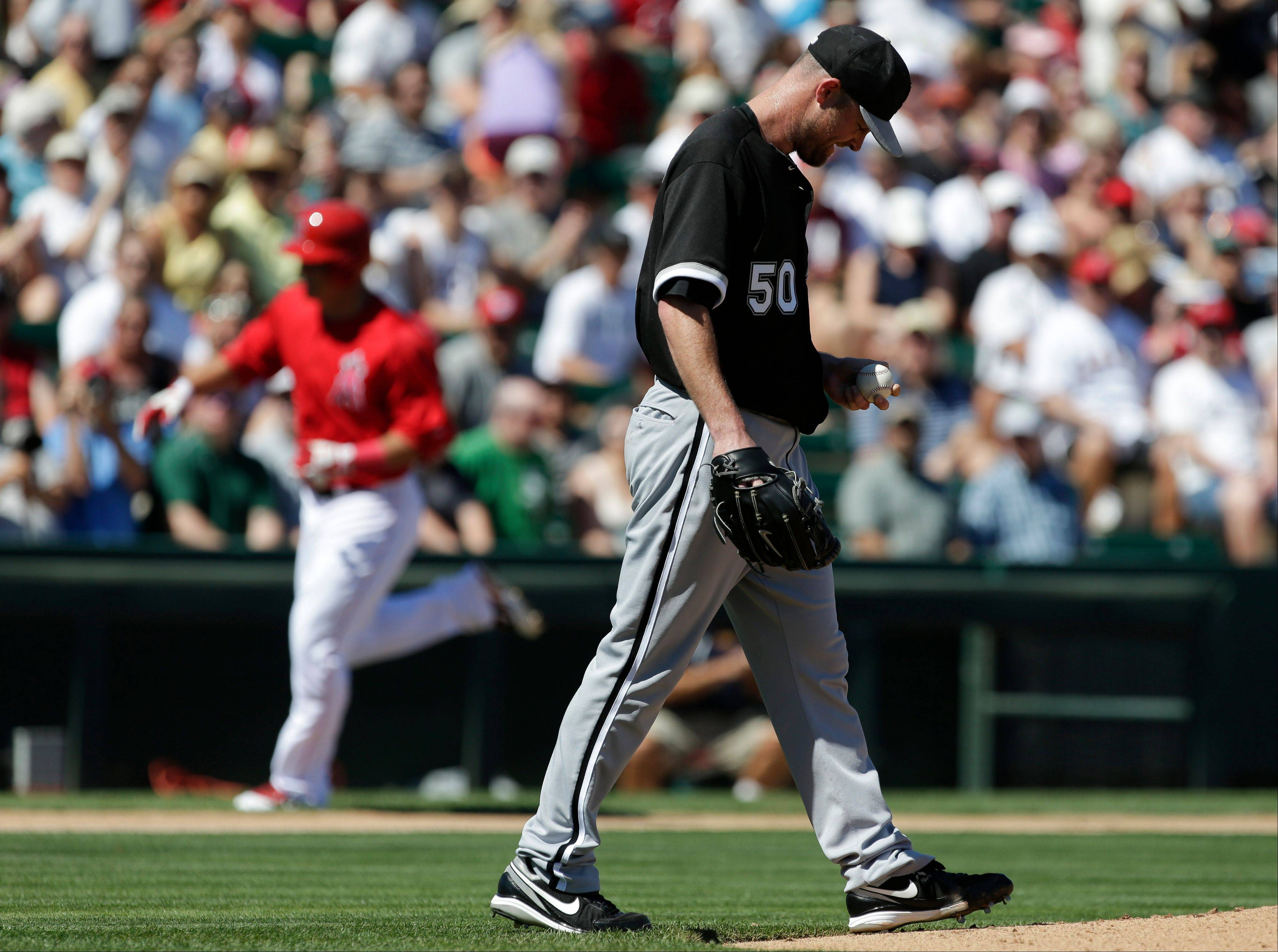 Los Angeles Angels' Mike Trout, back left, round the base after a home run as Chicago White Sox starting pitcher John Danks looks at the ball during the first inning of a spring training baseball game in Tempe, Ariz., Thursday, March 14, 2013. (AP Photo/Chris Carlson)