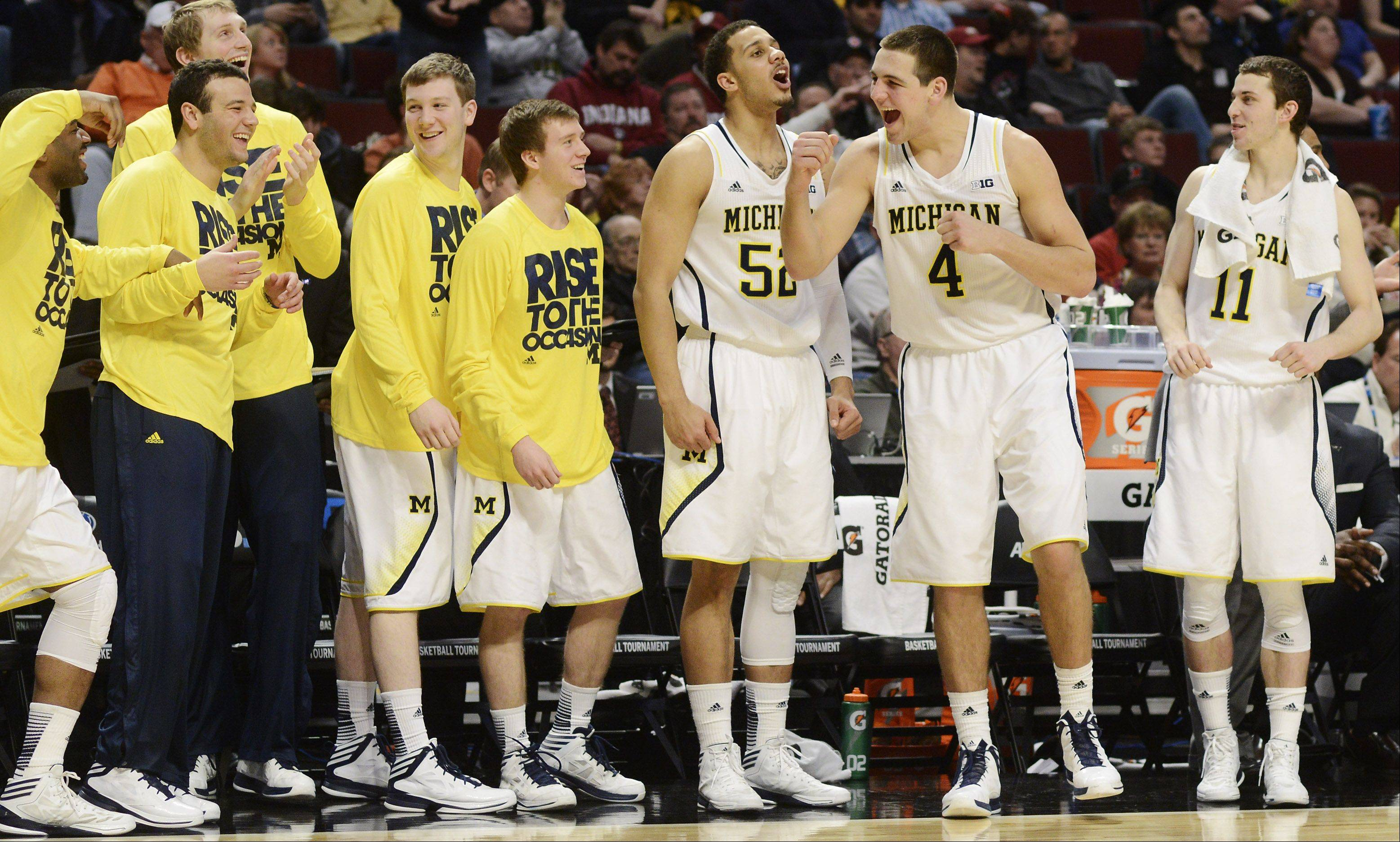 Players on the Michigan bench celebrate a basket-and-a-foul call.