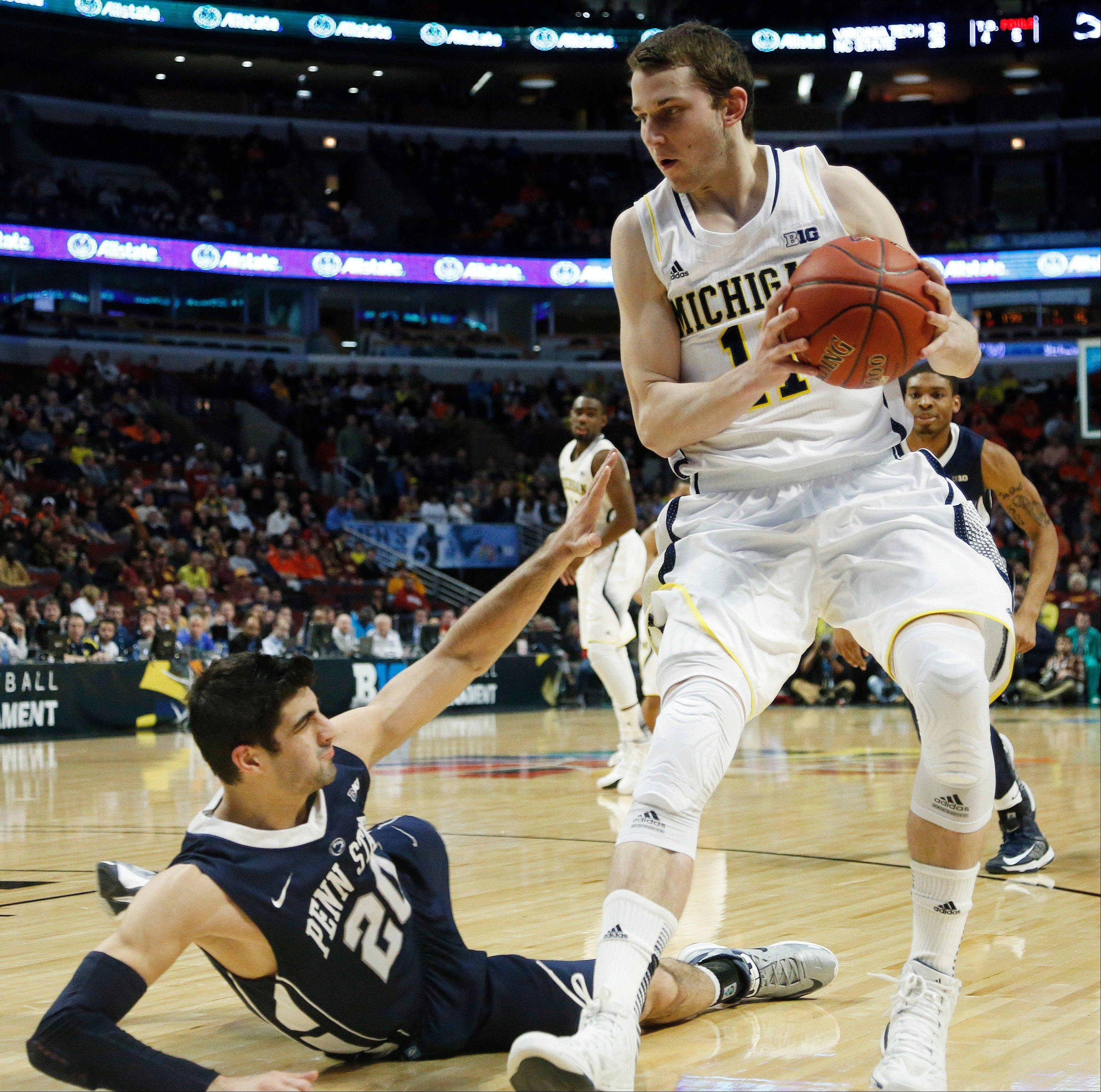Penn State�s Nick Colella falls as he defends Michigan�s Nik Stauskas Thrusday during the second half of an opening round game at the Big Ten tournament Thursday at the United Center.