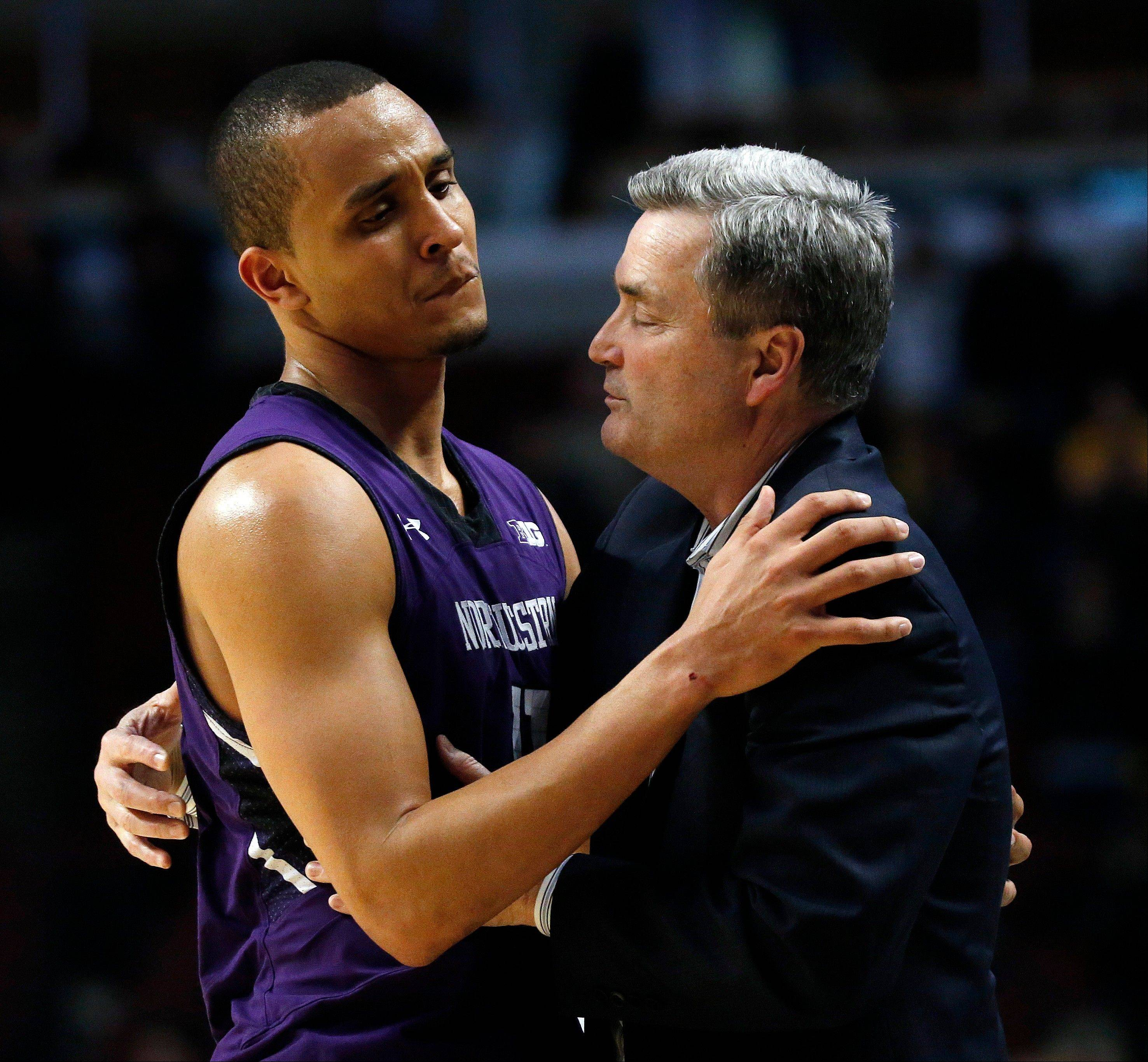 Northwestern head coach Bill Carmody hugs Reggie Hearn after an NCAA college basketball game at the Big Ten tournament against Iowa Thursday, March 14, 2013, in Chicago. Iowa won 73-59. (AP Photo/Charles Rex Arbogast)