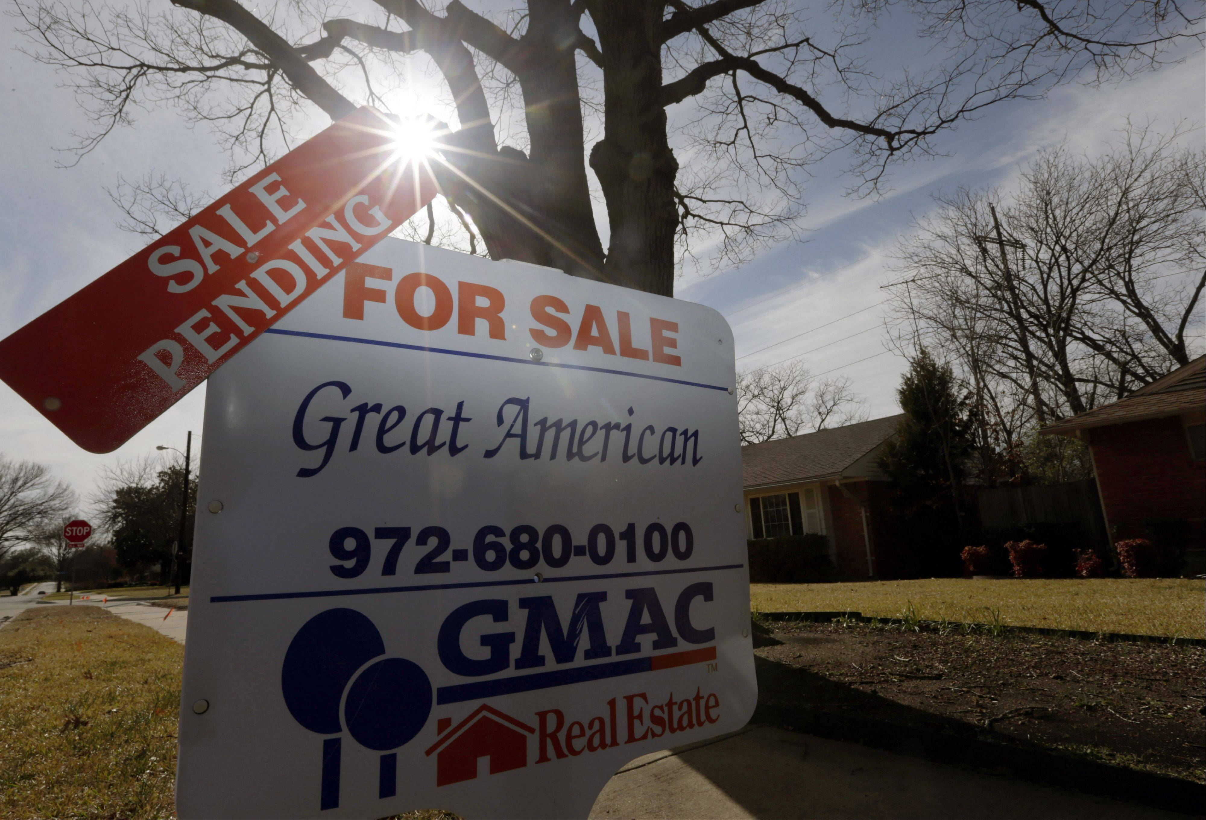 A sale pending announcement sits atop a for sale sign in a home's yard in Richardson, Texas.