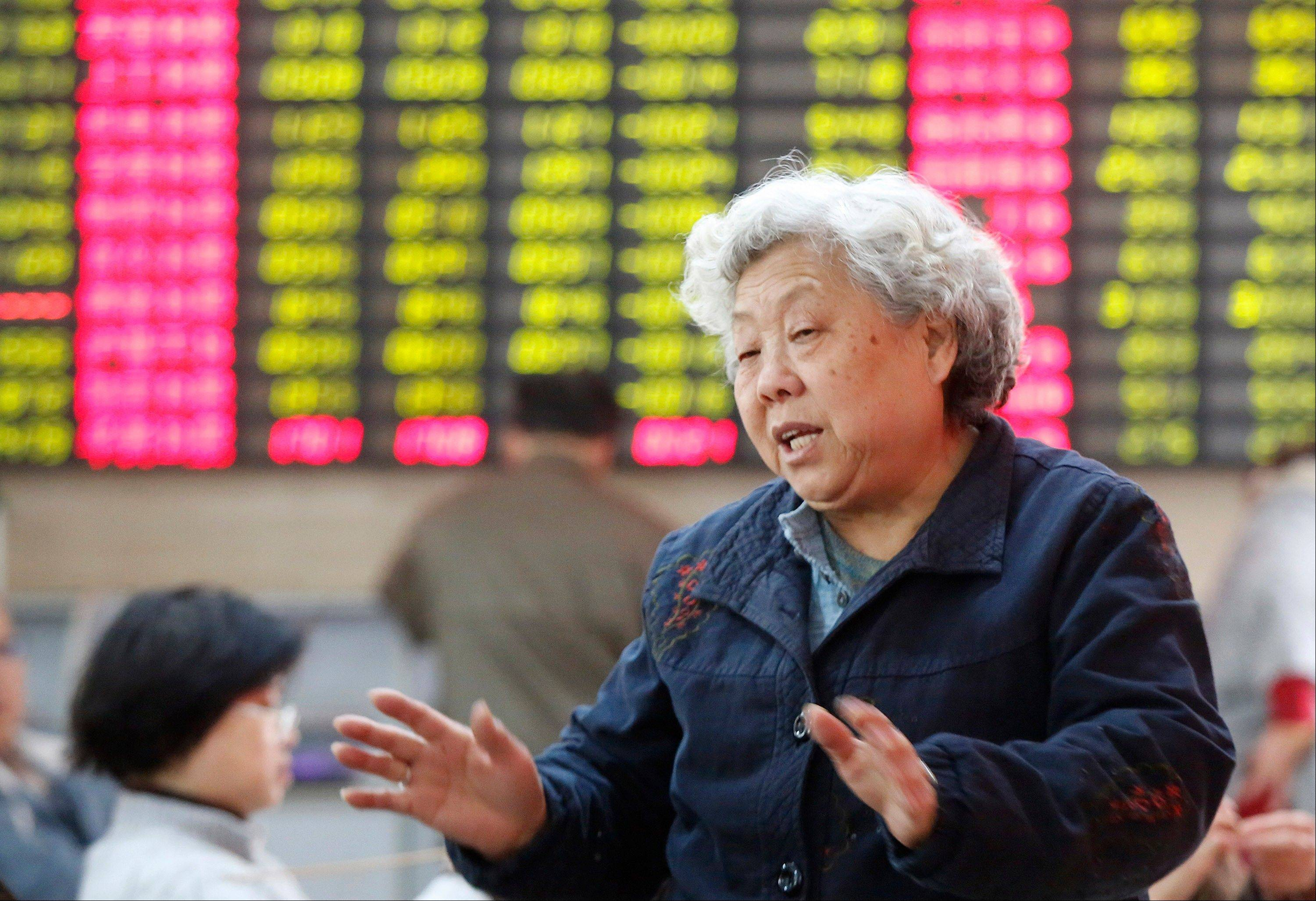 A woman chats with her fellow investor at a private securities company Tuesday in Shanghai, China.