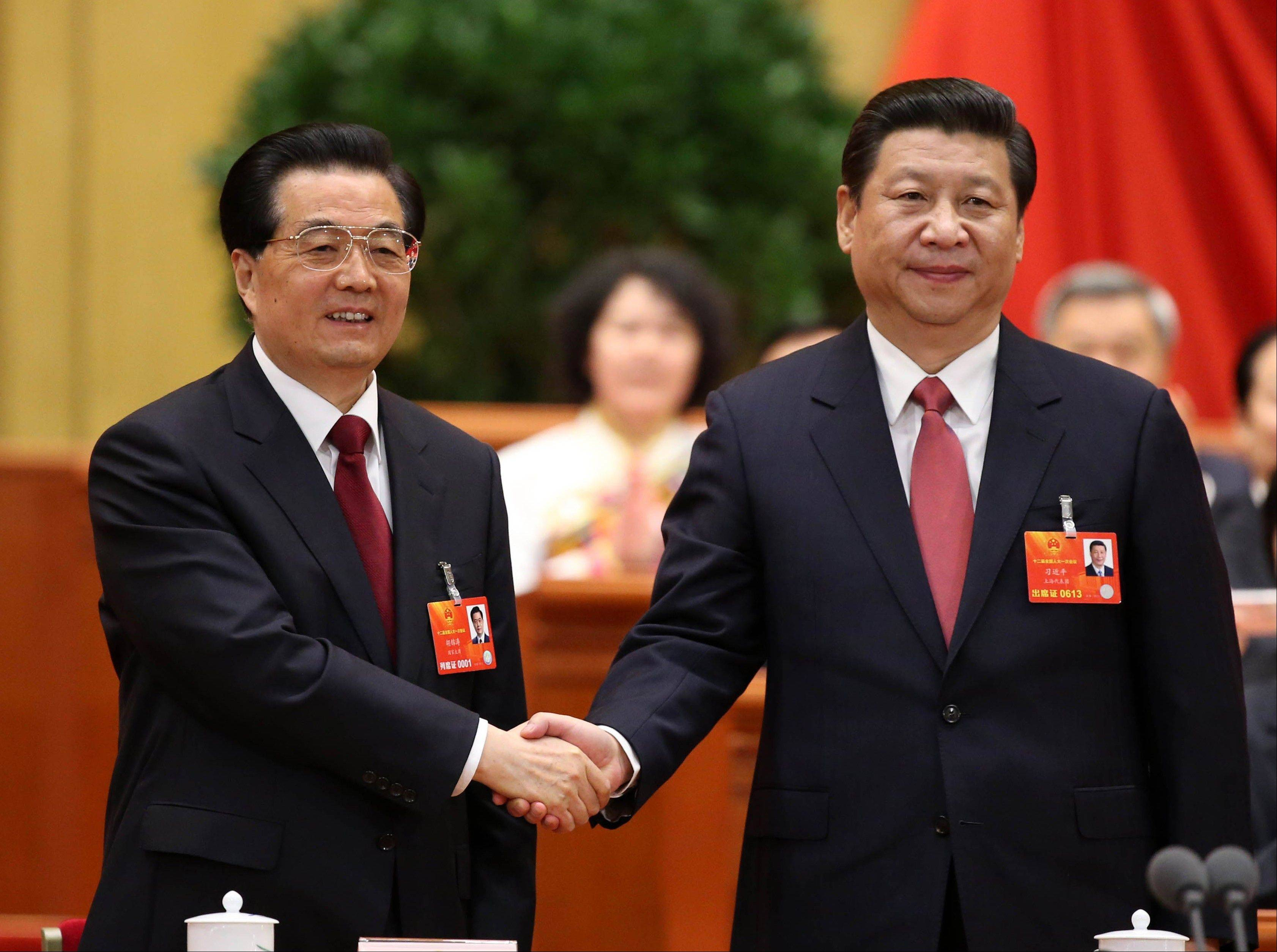 Outgoing Chinese President Hu Jintao, left, poses with his successor, Xi Jinping, after Xi was elected to the presidency at a plenary meeting of the National People's Congress in Beijing Thursday.