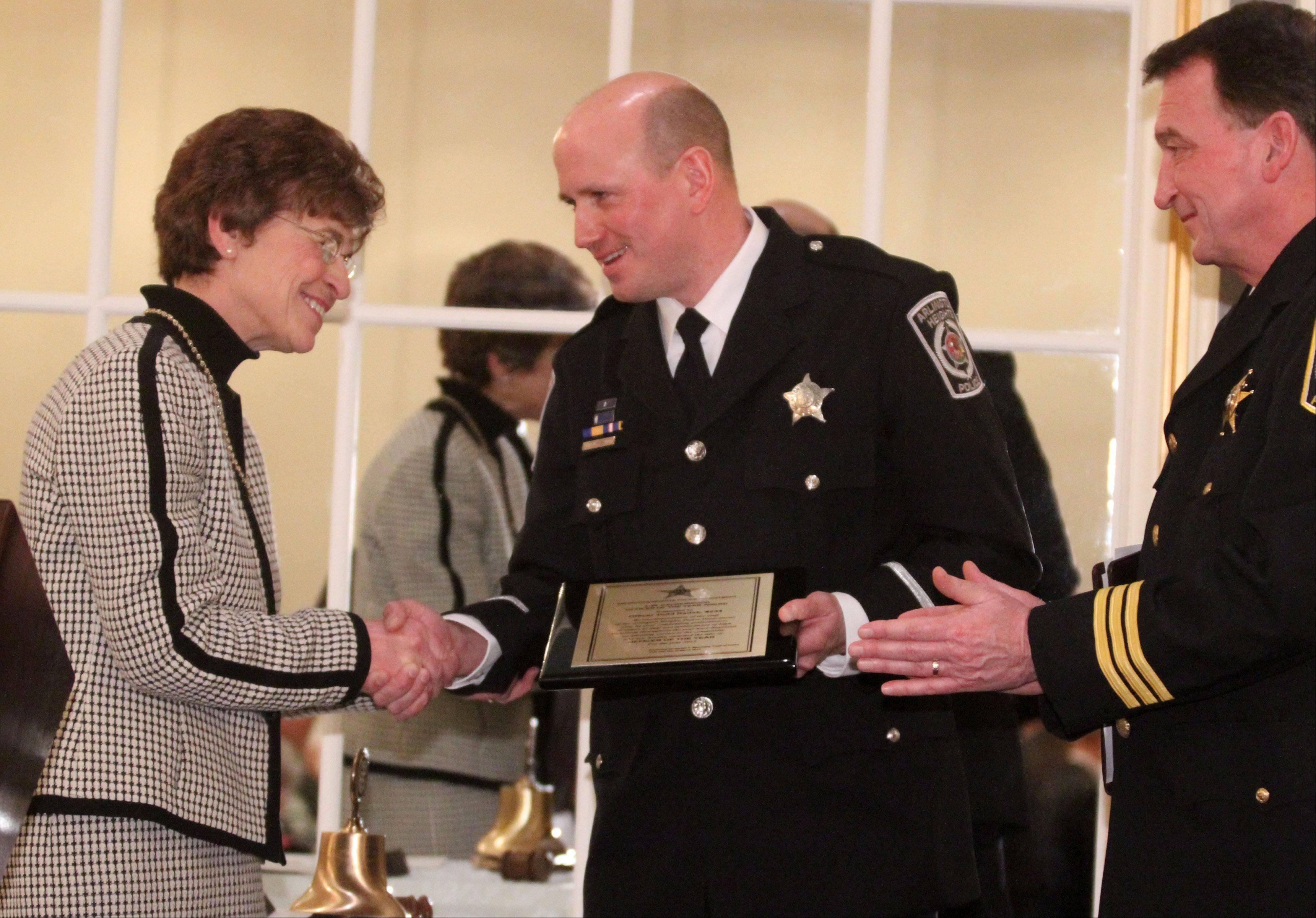Investigator Todd Radek, center, is congratulated by Arlington Heights Mayor Arlene J. Mulder, after receiving the 2012 Officer of the Year award from the Arlington Heights Rotary Club and Arlington Heights Police Chief Gerald Mourning, right.