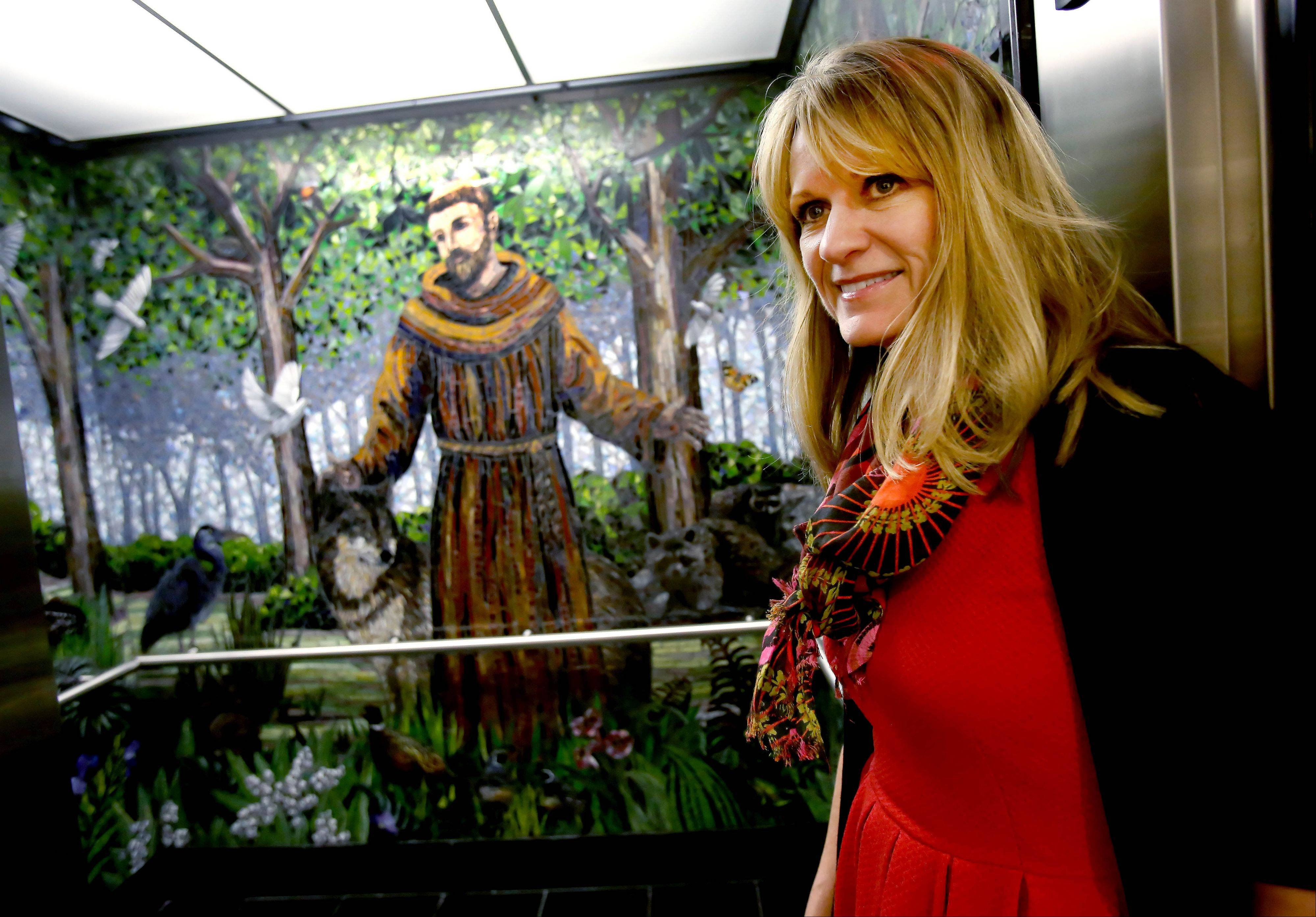 Diane Mercadante, director of pastoral ministry at St. Francis High School in Wheaton, talks about the new pope while standing by an elevator with a mosaic of St. Francis.