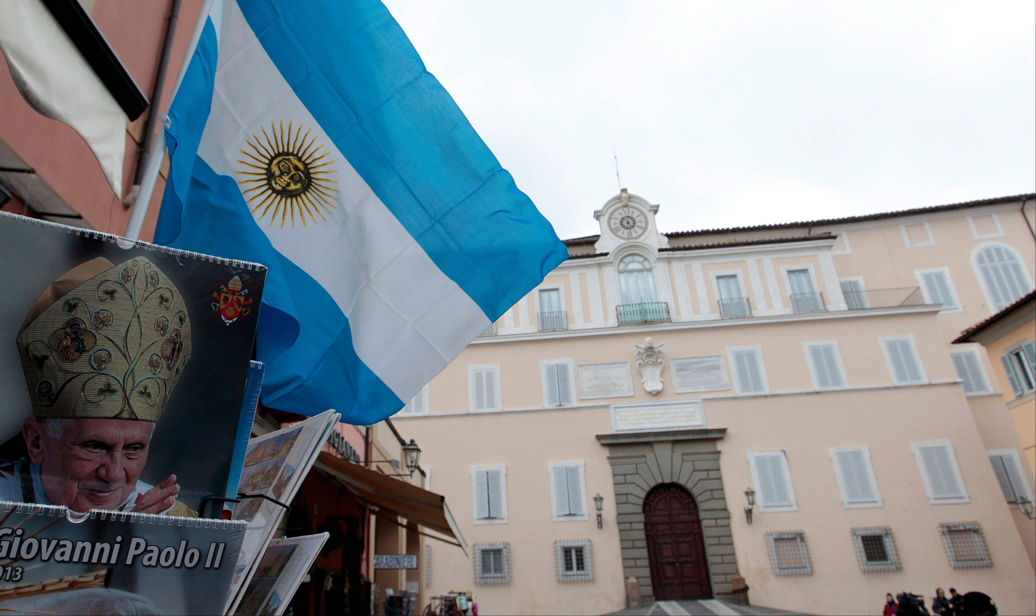 An Argentine flag waves from a stand displaying calendars of former Pope Benedict XVI outside the papal summer residence of Castel Gandolfo, Thursday, March 14, 2013.