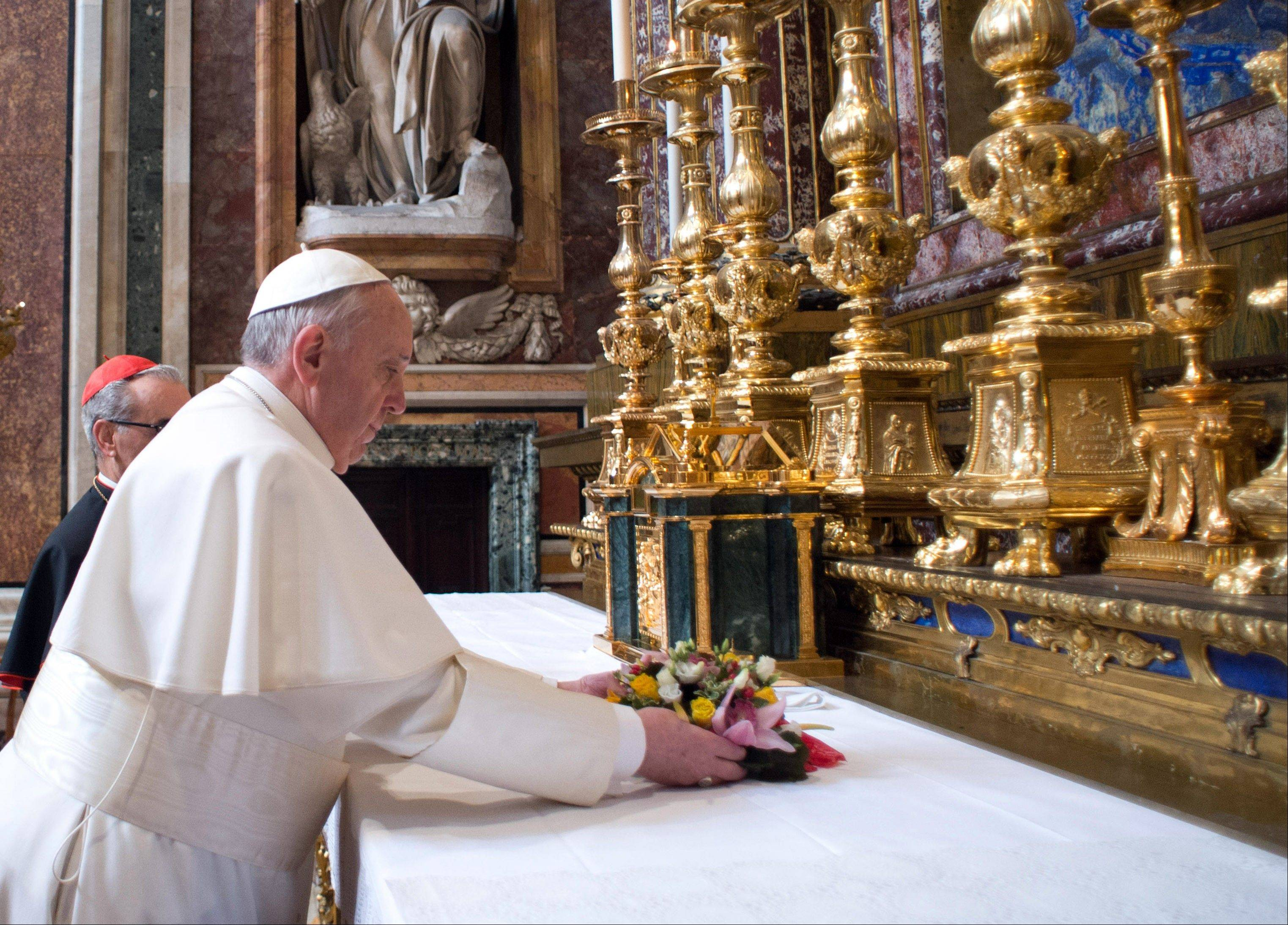Pope Francis puts flowers on the altar inside St. Mary Major Basilica, in Rome, Thursday, March 14, 2013. Pope Francis opened his first morning as pontiff by praying Thursday at Rome's main basilica dedicated to the Virgin Mary.