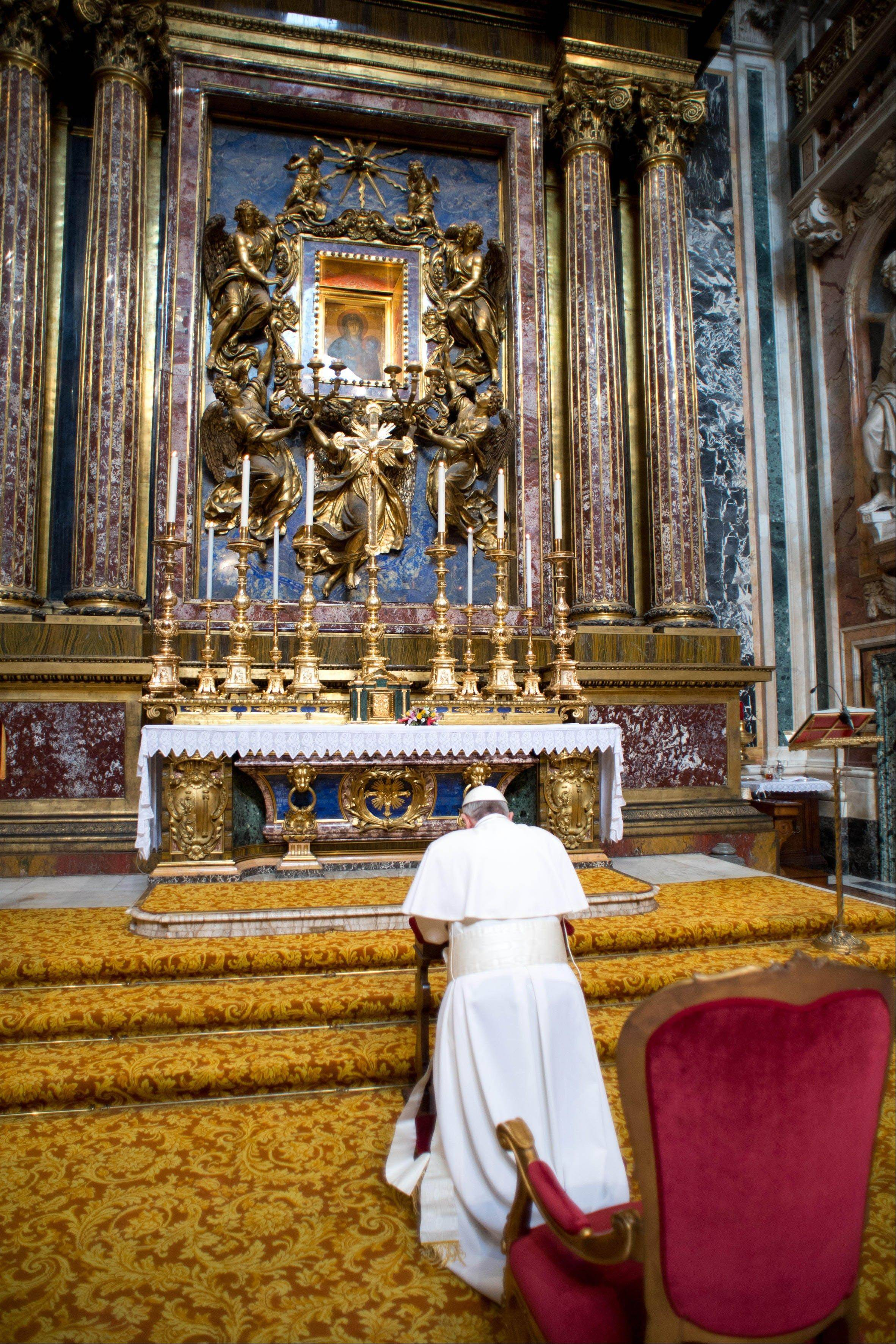 Pope Francis kneels in prayer in front of the icon of the Virgin Mary inside St. Mary Major Basilica, in Rome, Thursday, March 14, 2013. Pope Francis opened his first morning as pontiff by praying Thursday at Rome's main basilica dedicated to the Virgin Mary, a day after cardinals elected him the first pope from the Americas.